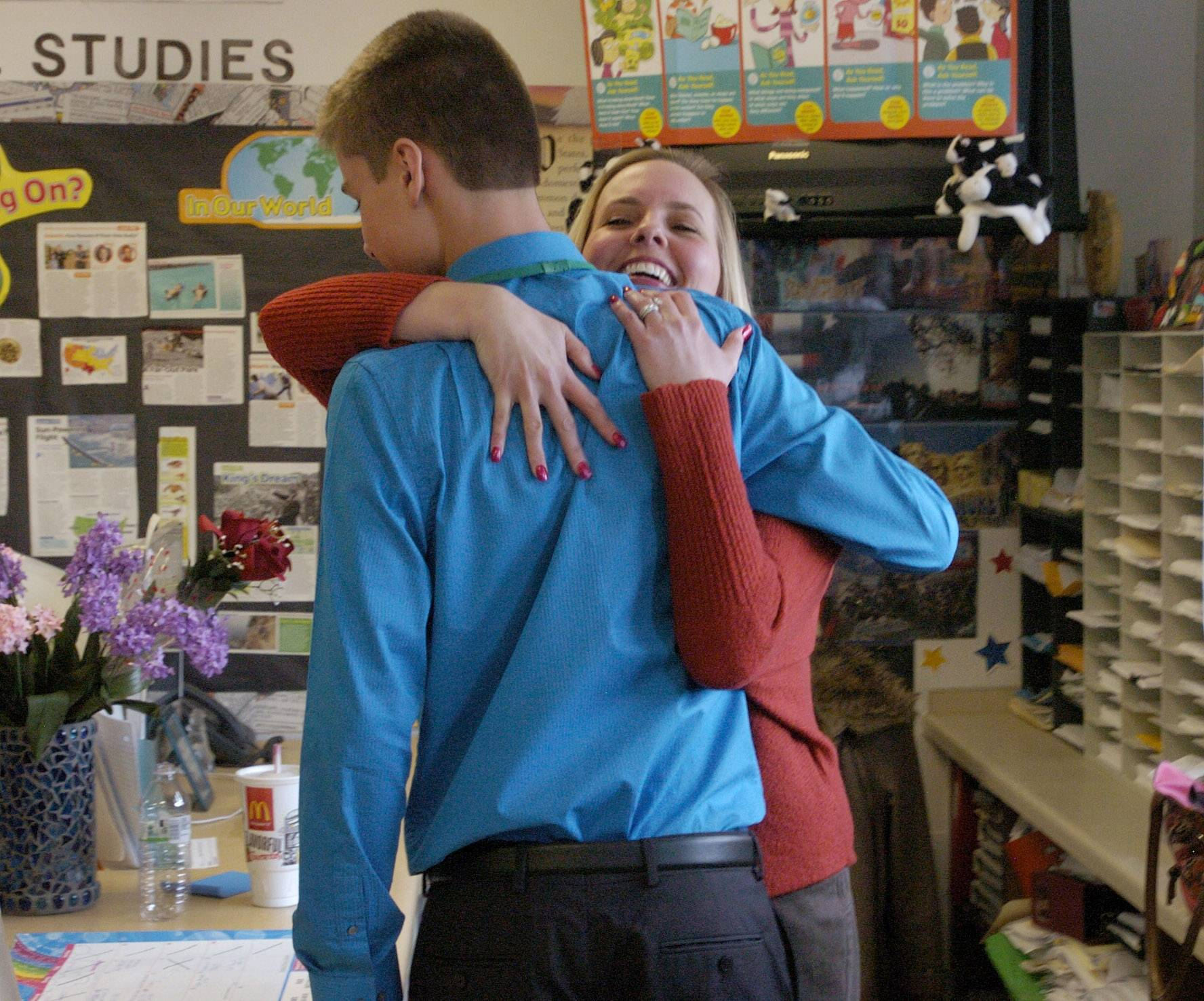 Woodland Middle School seventh grader Bradley Wilinski was superintendent for a day on Tuesday. Katie Herren, his former 4th grade teacher, gives Bradley a hug after he talked to her fifth graders.