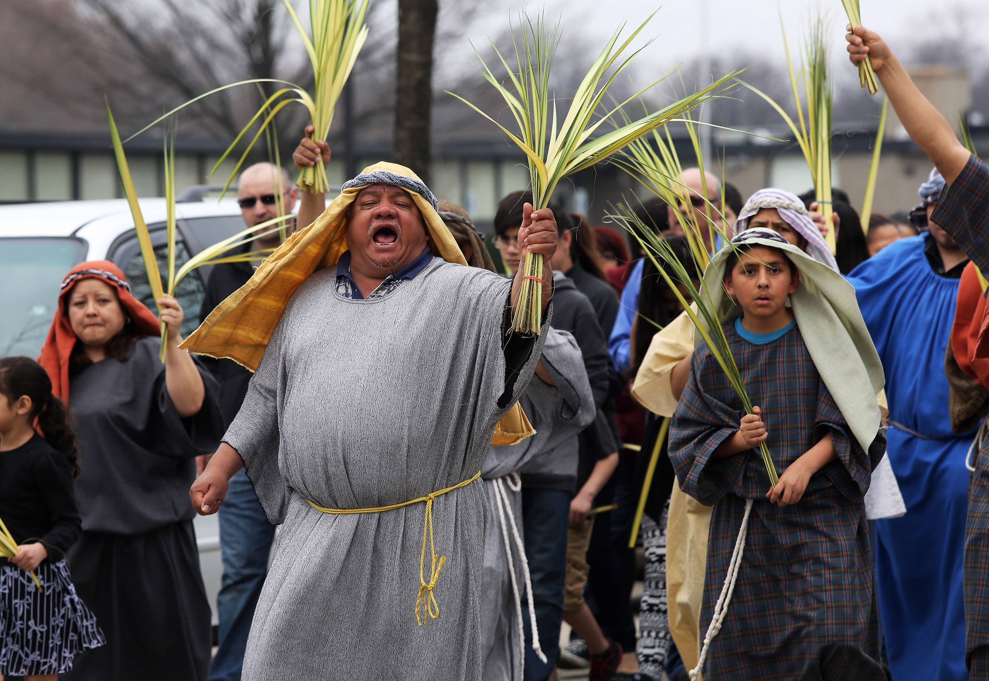 Antonio Vargas, of Palatine, chants as he walks with parishioners in a Palm Sunday procession from St. Thomas Villanova in Palatine to Mission San Juan Diego in Arlington Heights.
