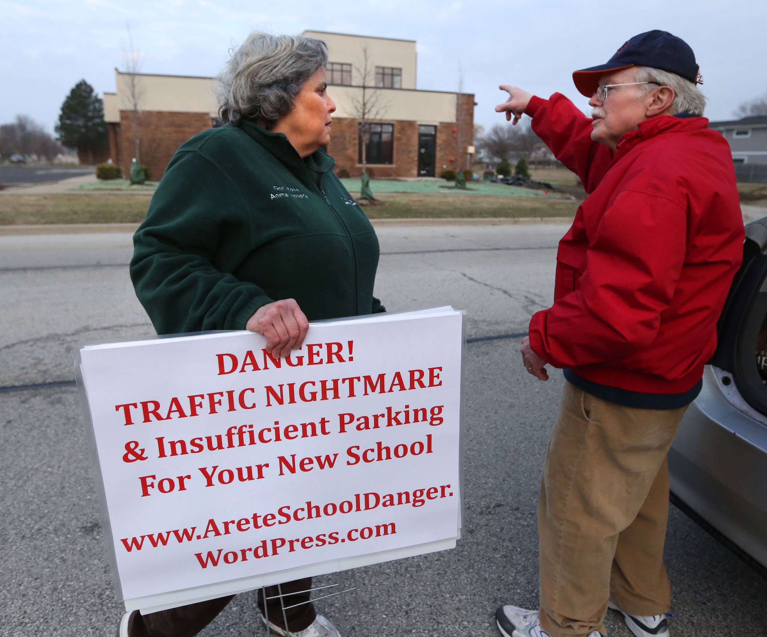 Bob Bacon and his wife Karen Hailpern, of unincorporated Cook County, prepare to place signs around Montessori School in Hoffman Estates for an informational picket on Tuesday about the owner's plans to add another location at a site picketers don't approve of.