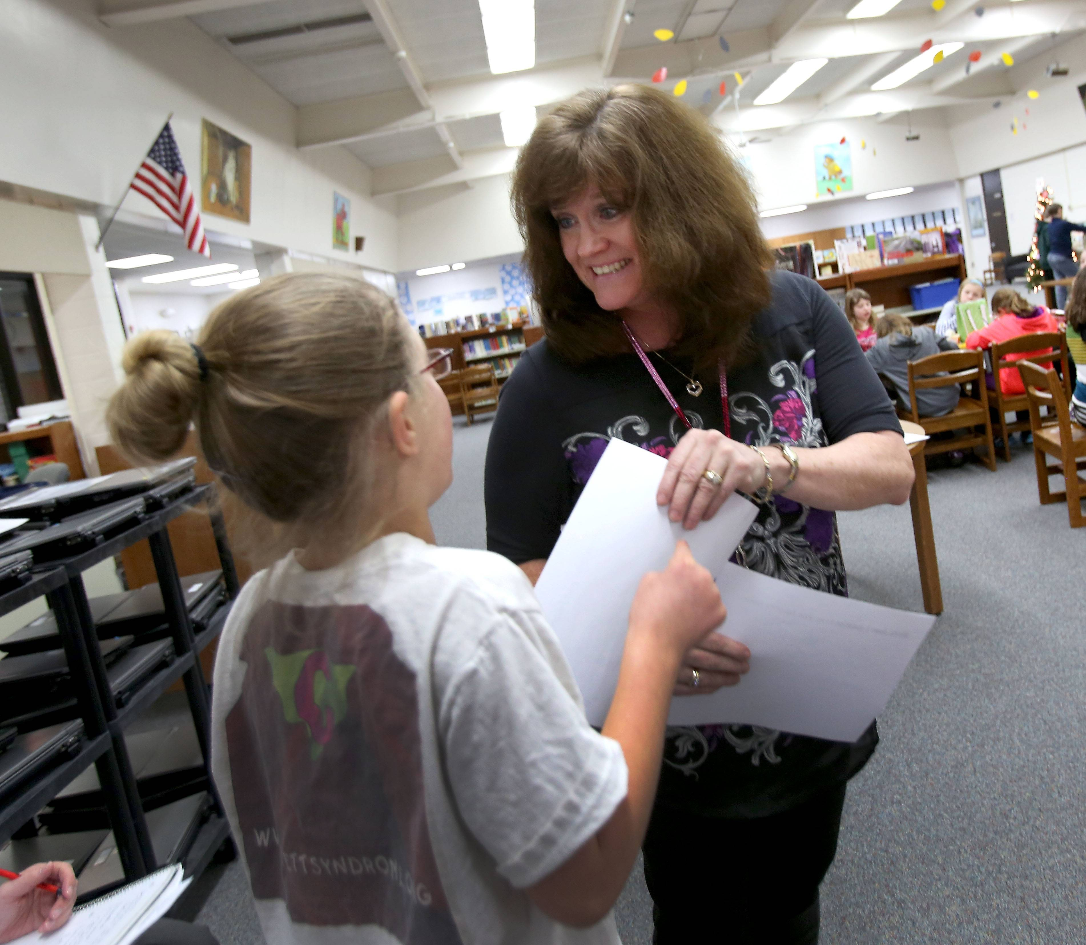 "Student Carly Cernek chats with Jeni Rogers in their Prairie Elementary School classroom. Rogers says fifth-graders can be challenging, but they're also funny, inquisitive, ""and I love to see the growth."""