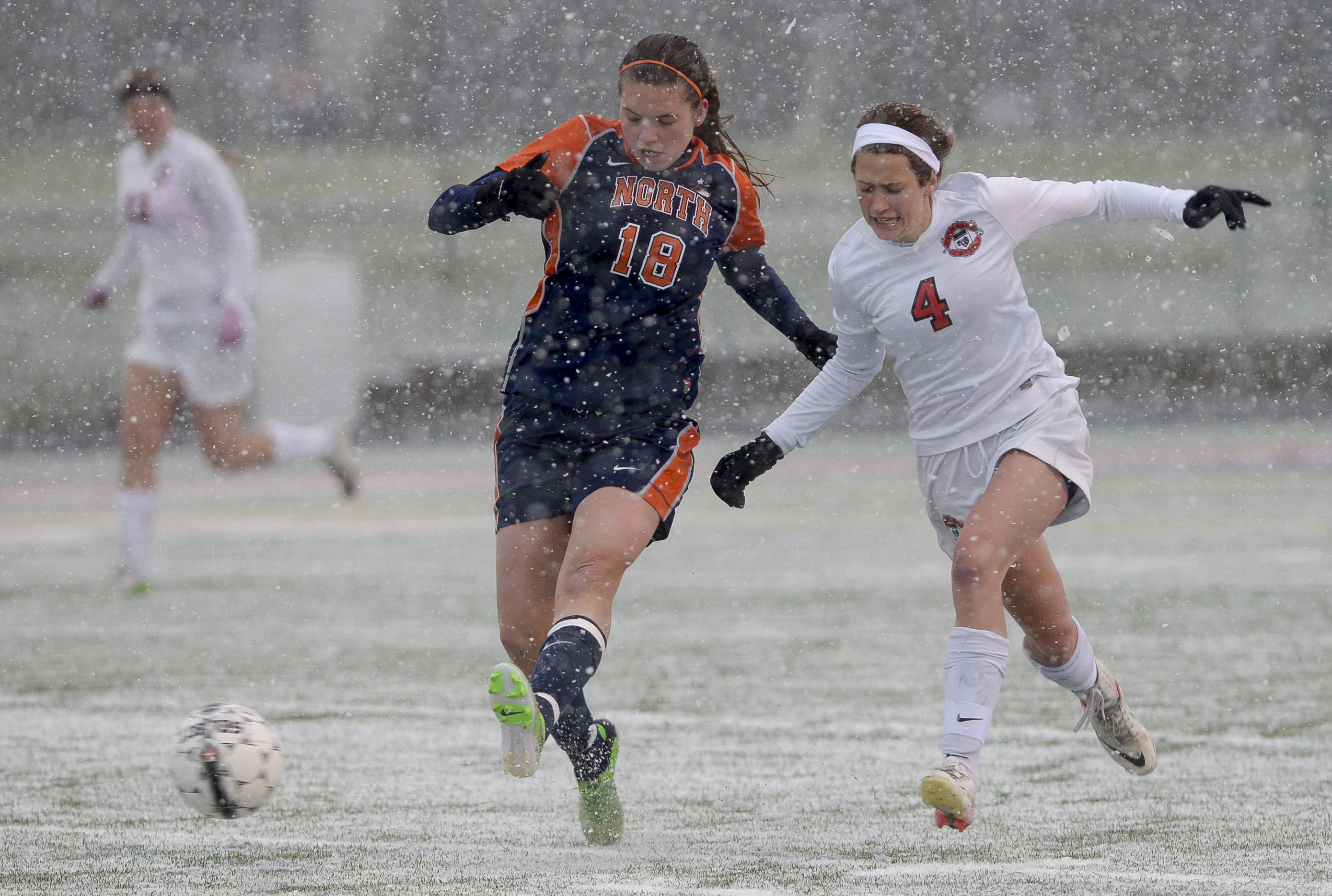 Naperville North's Morgan Krause and Glenbard East's Alex Ruffer chase down the ball, through heavy snow, during the Huskies 2-0 win over the Rams in Lombard Monday.