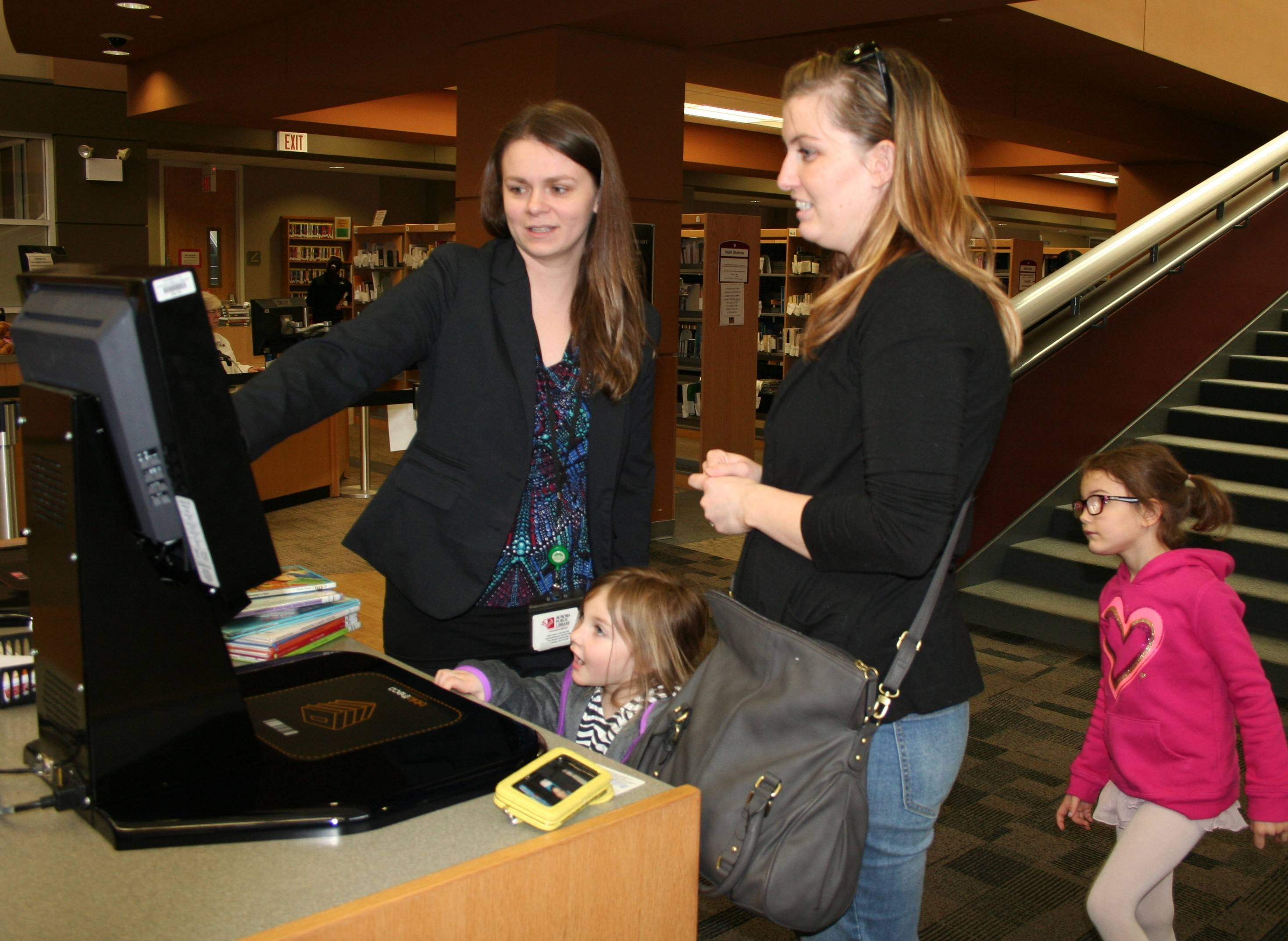Eola Road Branch Circulation Manager Crissy Barnat helps Brittany Macaulay check out books on the new self-check system.