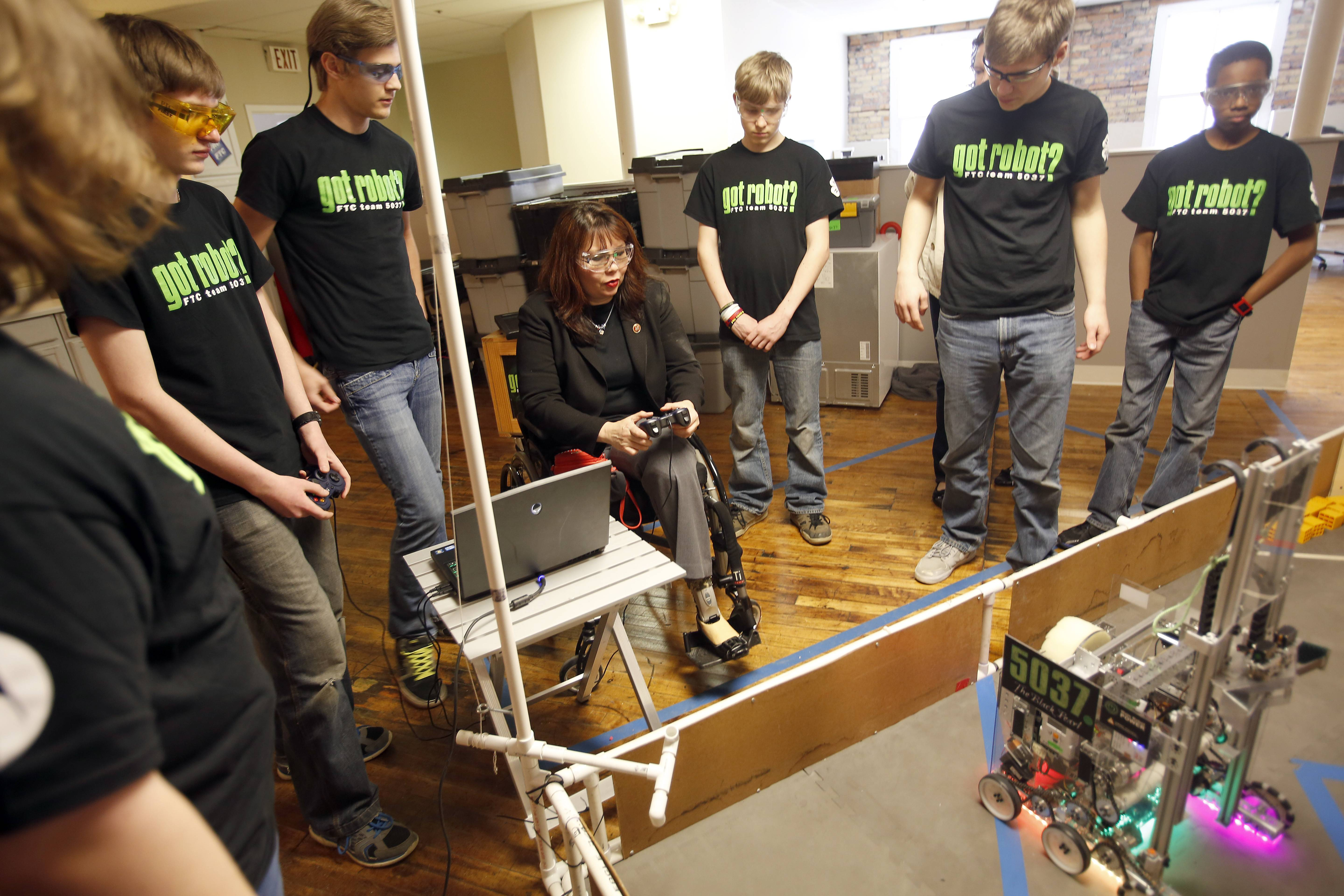 "Surrounded by members of the got robot? First Tech Challenge 5037 robotics team, U.S. Rep. Tammy Duckworth drives a robot called the ""Black Pearl"" at the Elgin Technology Center Wednesday."