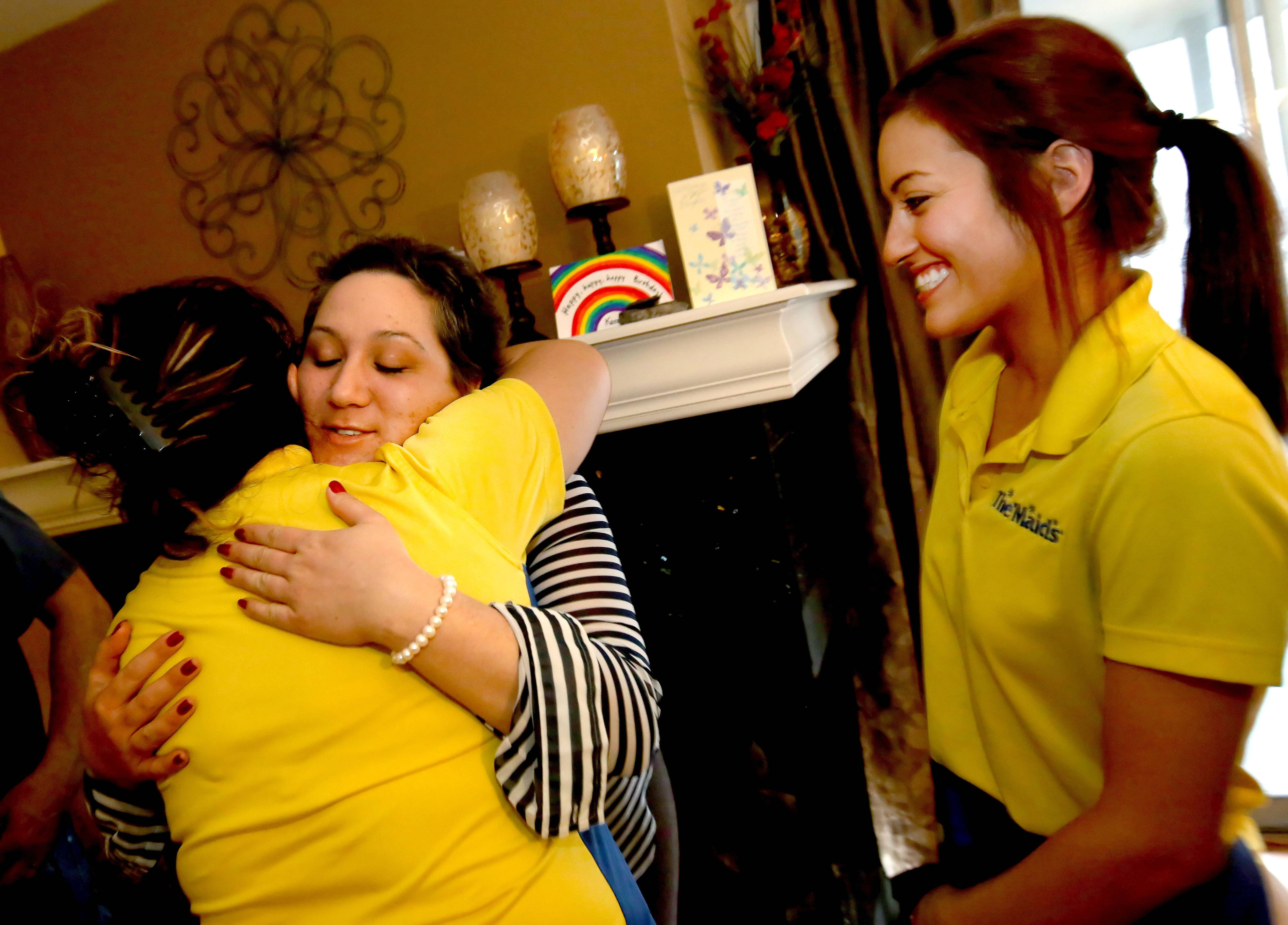 Kara Colantuono gives Sarah Buhle of The Maids of DuPage County a hug as Aracelli Garcia, right, looks on, after they cleaned Colantuono's condo in Wheaton. The maid service is partnering with Cleaning for a Reason Foundation to provide free house cleaning services to women undergoing cancer treatment.