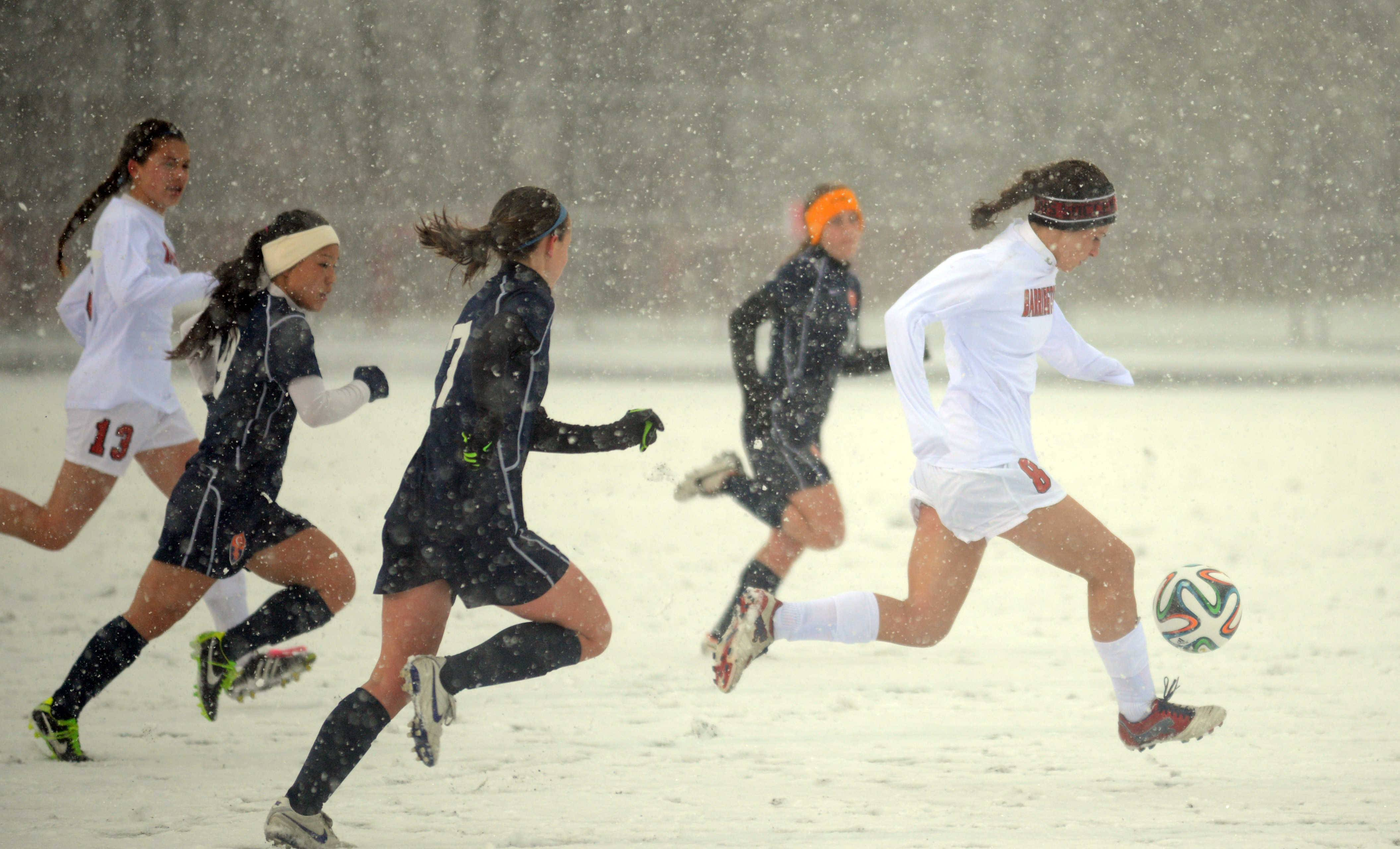 Soccer in the snow: Barrington's Maesyn Poidomani, right, moves the ball against Buffalo Grove during a varsity girls soccer match at Coach Tom Frederick Field last night in Barrington.