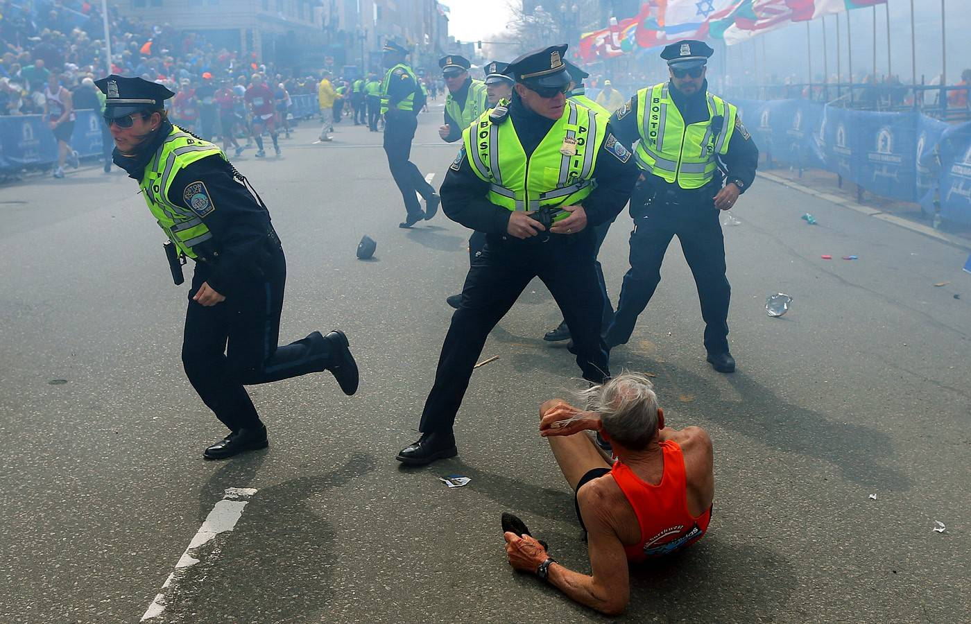 Bill Iffrig, 78, lies on the ground as police officers react to a second explosion at the finish line of the Boston Marathon in Boston. Iffrig, of Lake Stevens, Wash., was running his third Boston Marathon and near the finish line when he was knocked down by one of the two bomb blasts.