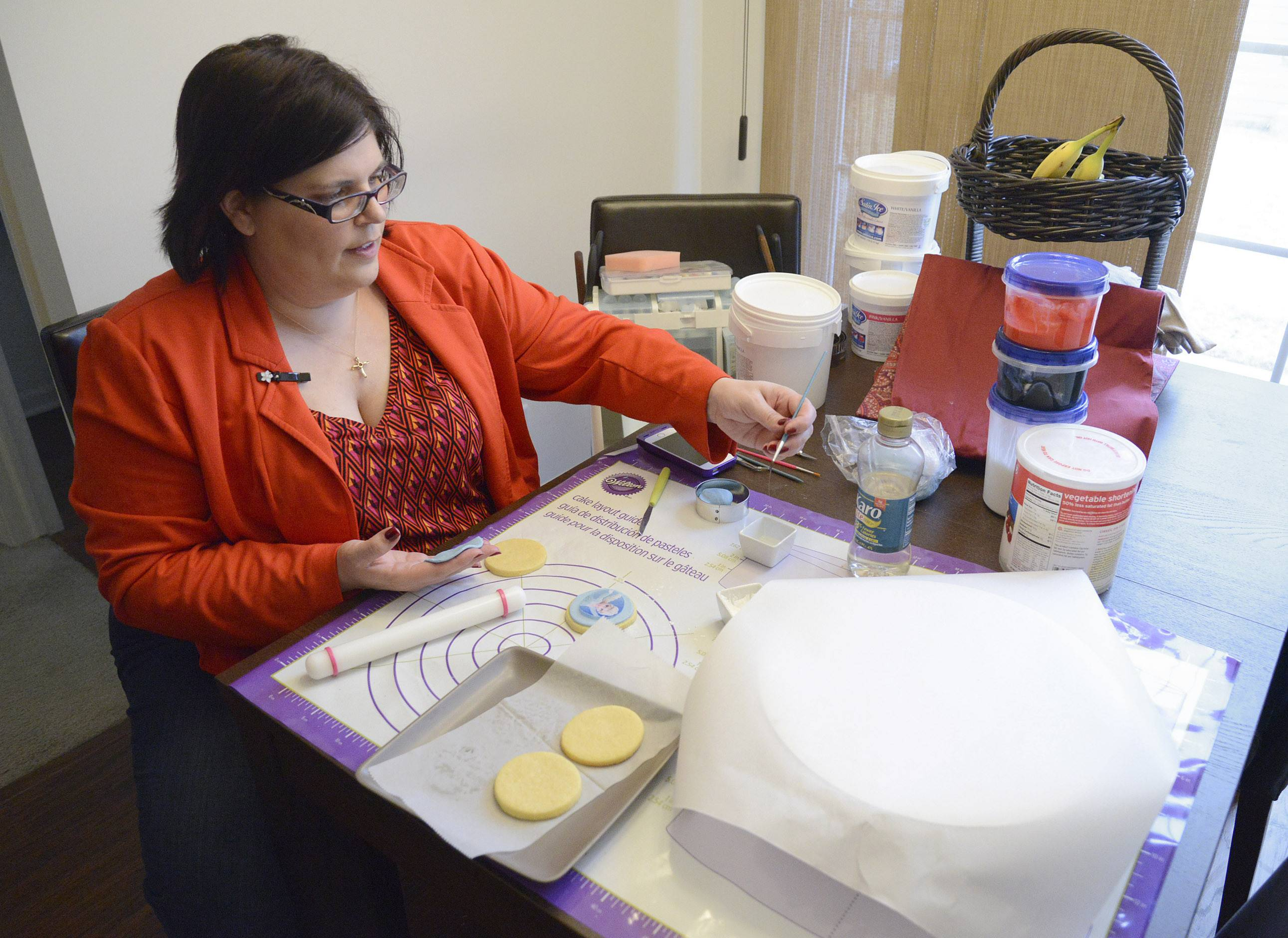 Christina Hernandez of Elgin decorates butter cookies for customers of her FanCThatEvents cookie shop on Etsy.com.
