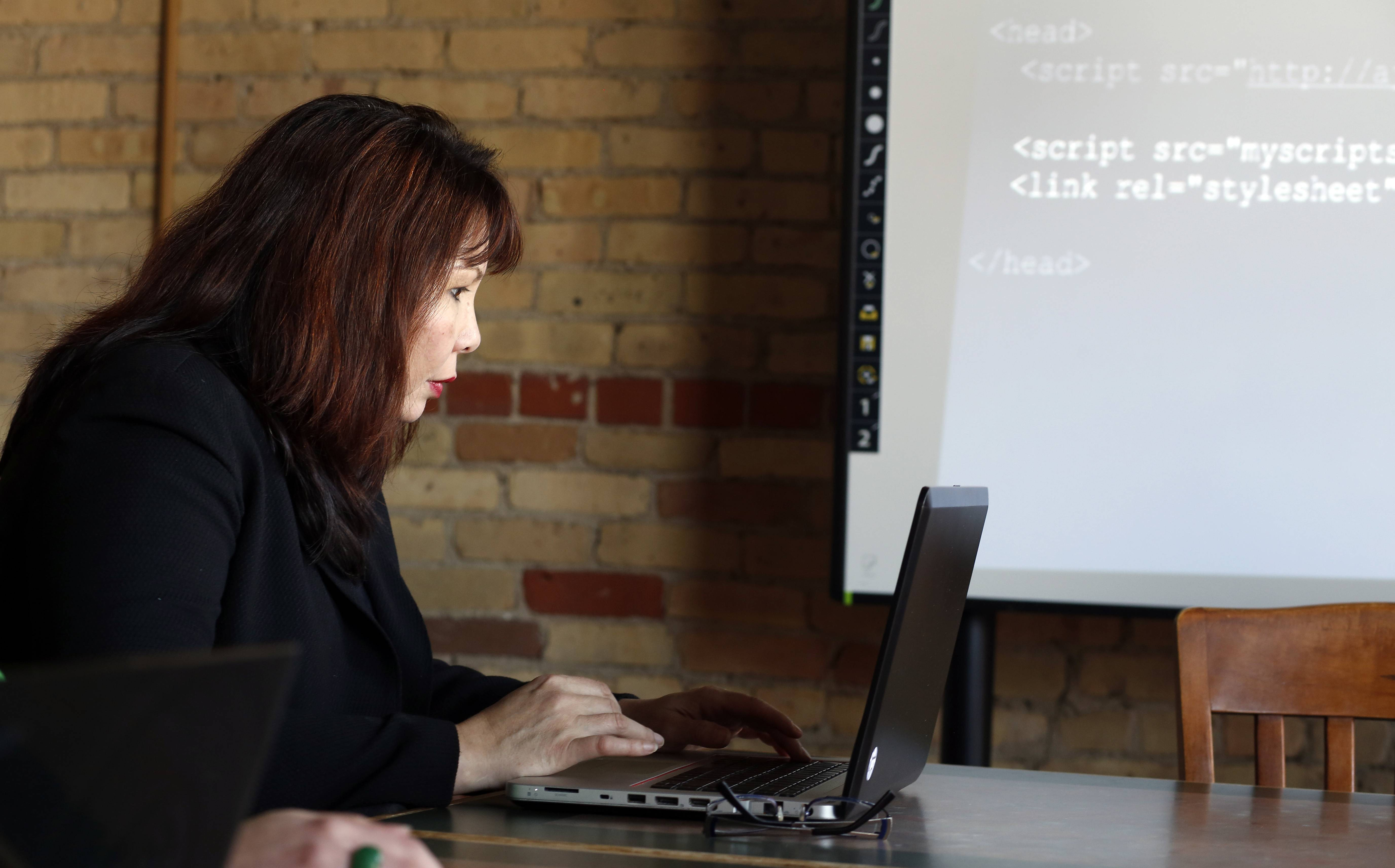 U.S. Rep. Tammy Duckworth learns how to code an app during a visit to the Elgin Technology Center Wednesday to promote the House Student App Challenge.