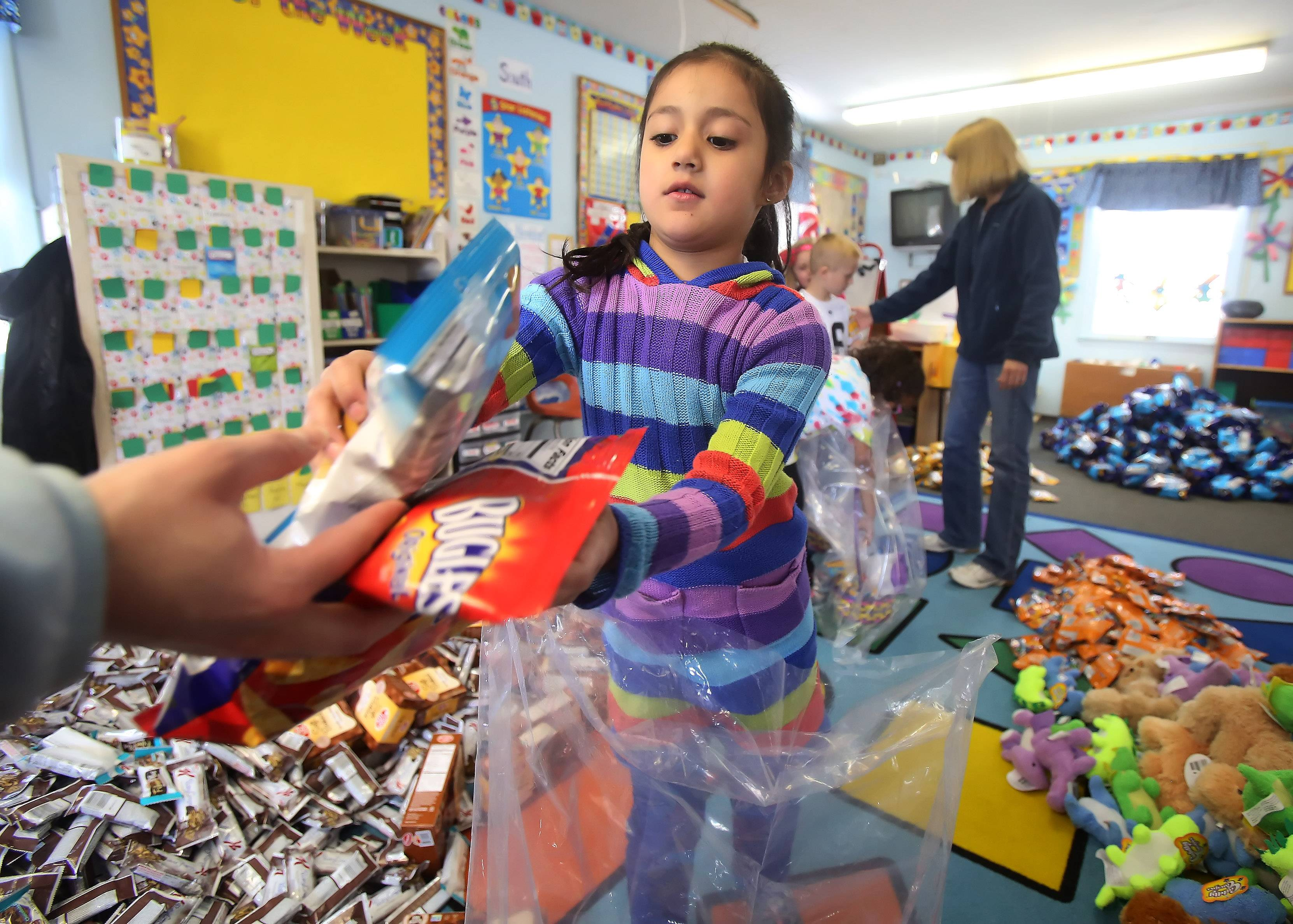 Kindergartner Maya Rodriguez takes food to make a spring basket Tuesday at the Lindenhurst Early Childhood Center. Five hundred baskets will be distributed to less fortunate children through Lake County Housing Authority, area food pantries, PADS and other groups.