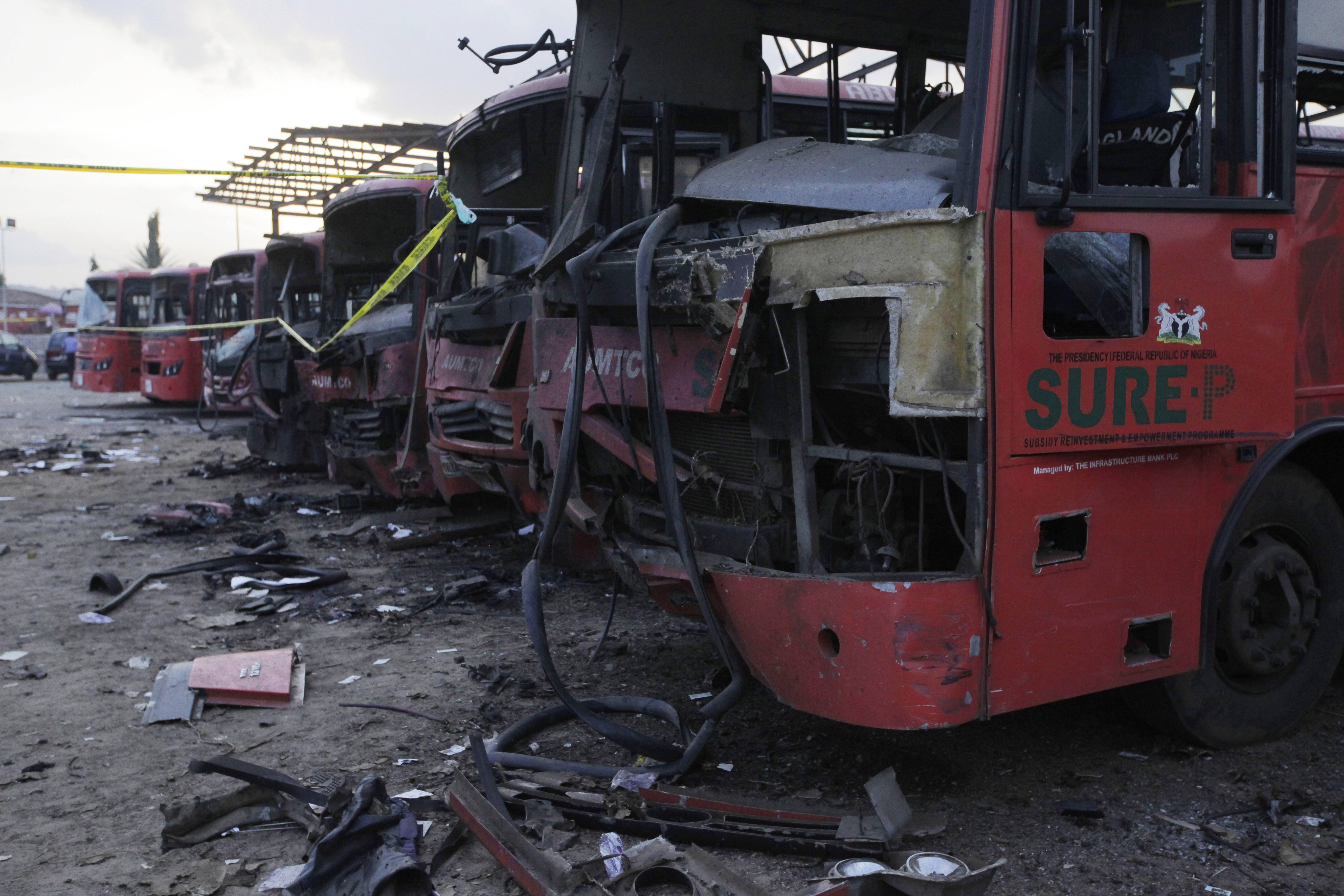 Damaged buses are seen at the scene of an explosion at a bus park in Abuja, Nigeria, Monday, April. 14, 2014. The toll from the massive explosion in Nigeria's capital rose to 75 dead Tuesday and is expected to grow.