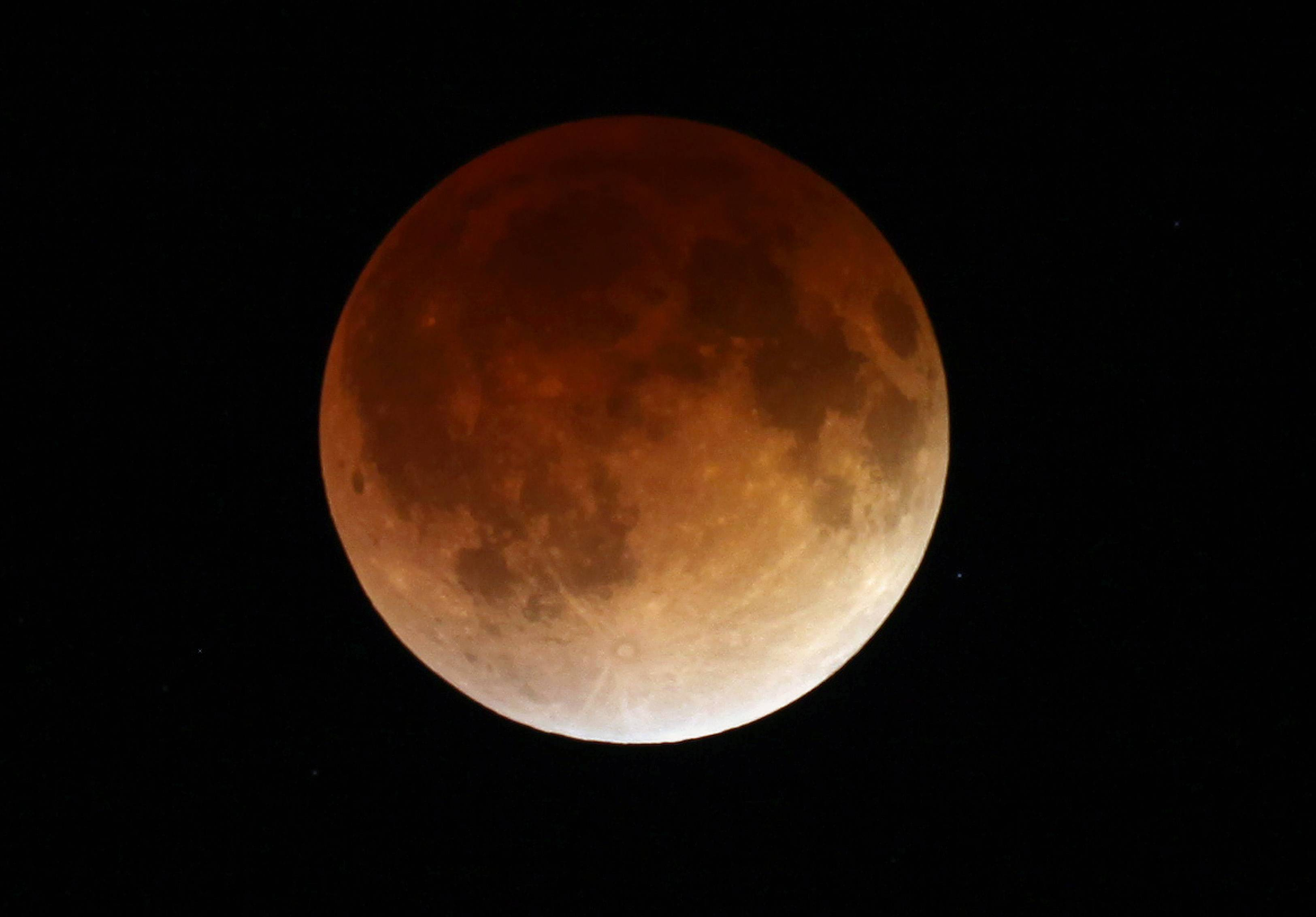 The moon glows a red hue during a total lunar eclipse Tuesday, April 15, 2014, as seen from the Milwaukee area. Tuesday's eclipse is the first of four total lunar eclipses that will take place between 2014 to 2015.