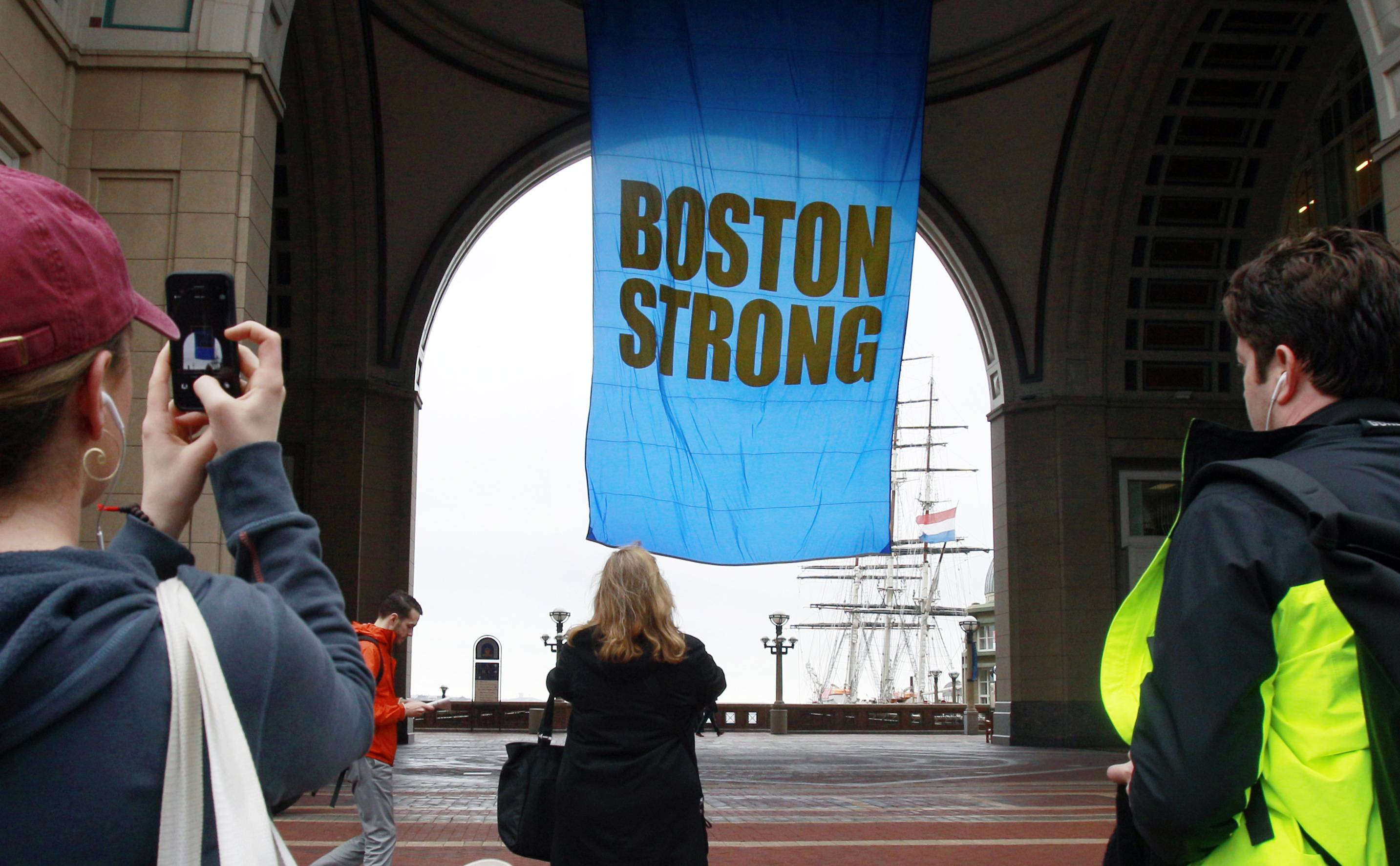 "People photograph a banner reading ""Boston Strong"" Tuesday as it hangs at Rowes Wharf on the first anniversary of the Boston Marathon bombings in Boston."