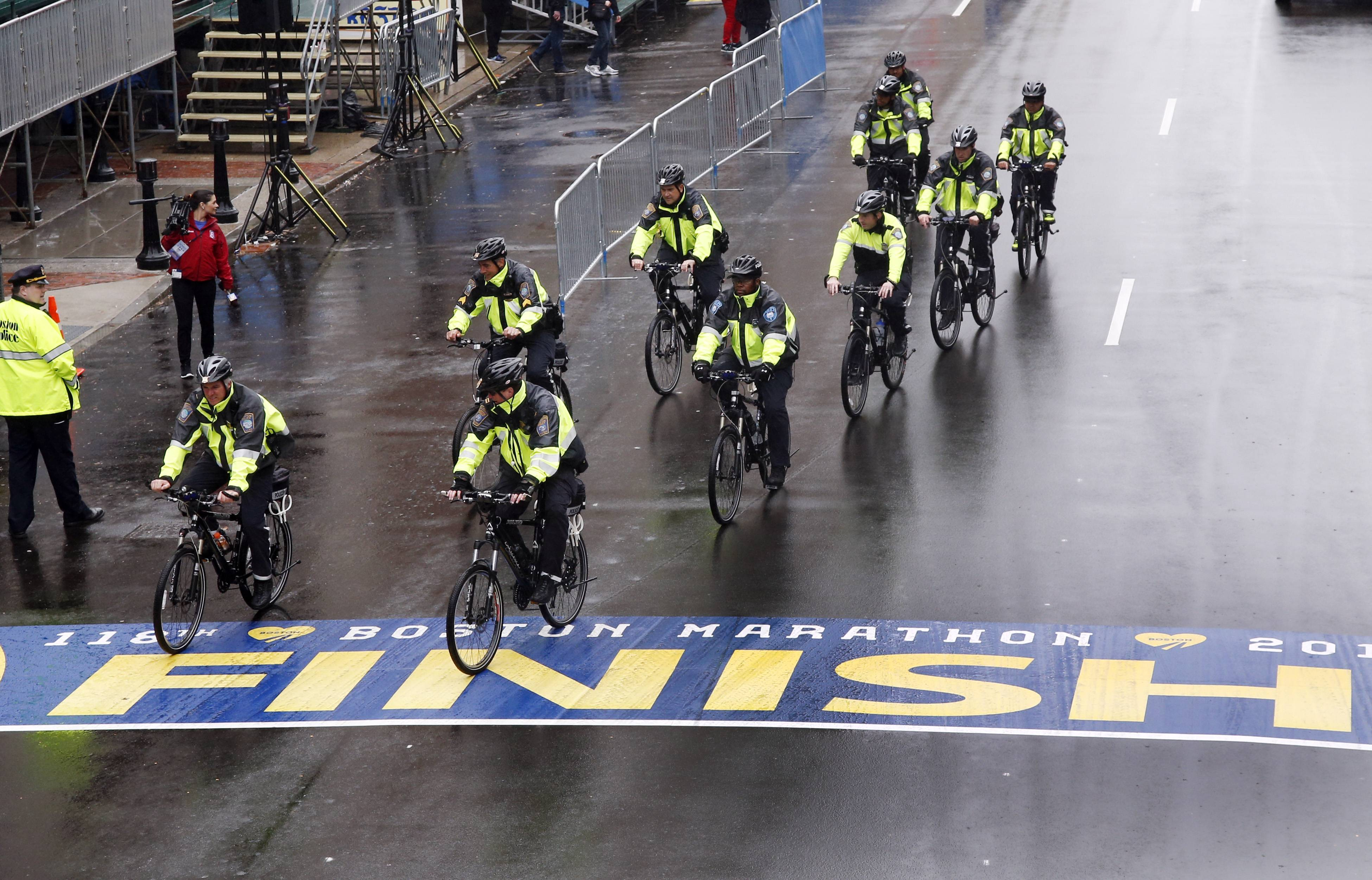 Police on bikes cycle across the Boston Marathon finish line Tuesday prior to a remembrance ceremony for family members and survivors of the 2013 Boston Marathon bombing on Boylston Street in Boston.