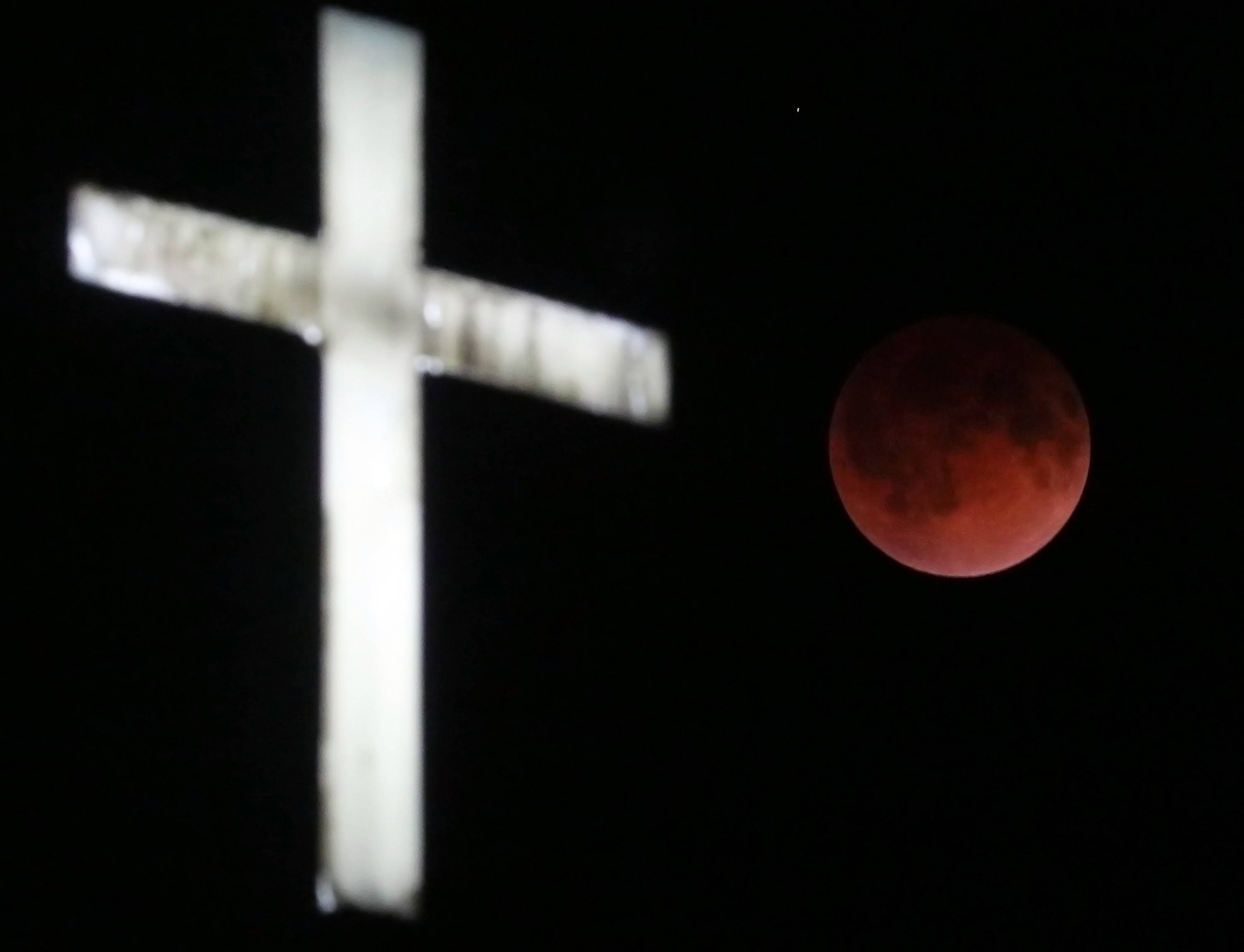 The Earth's shadow renders the moon in a crimson hue during a total lunar eclipse behind the illuminated steeple of St. Olaf Lutheran Church in the town of Ashippun, Wis. Tuesday, April 15, 2014.