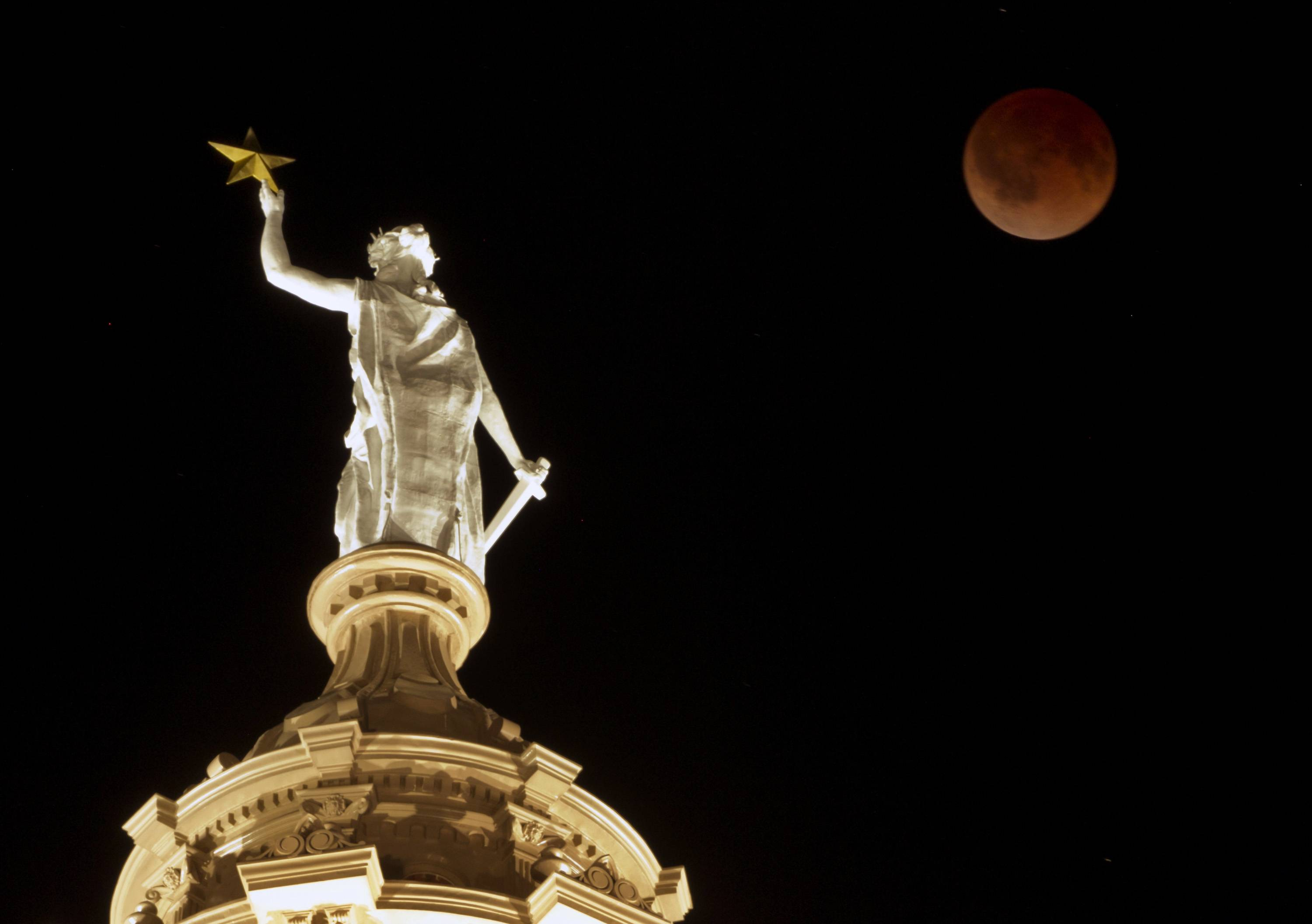 The moon glows a red hue over the Goddess of Liberty statue atop the Capitol in Austin, Texas, during a total lunar eclipse Tuesday, April 15, 2014. Tuesday's eclipse is the first of four total lunar eclipses that will take place between 2014 to 2015.