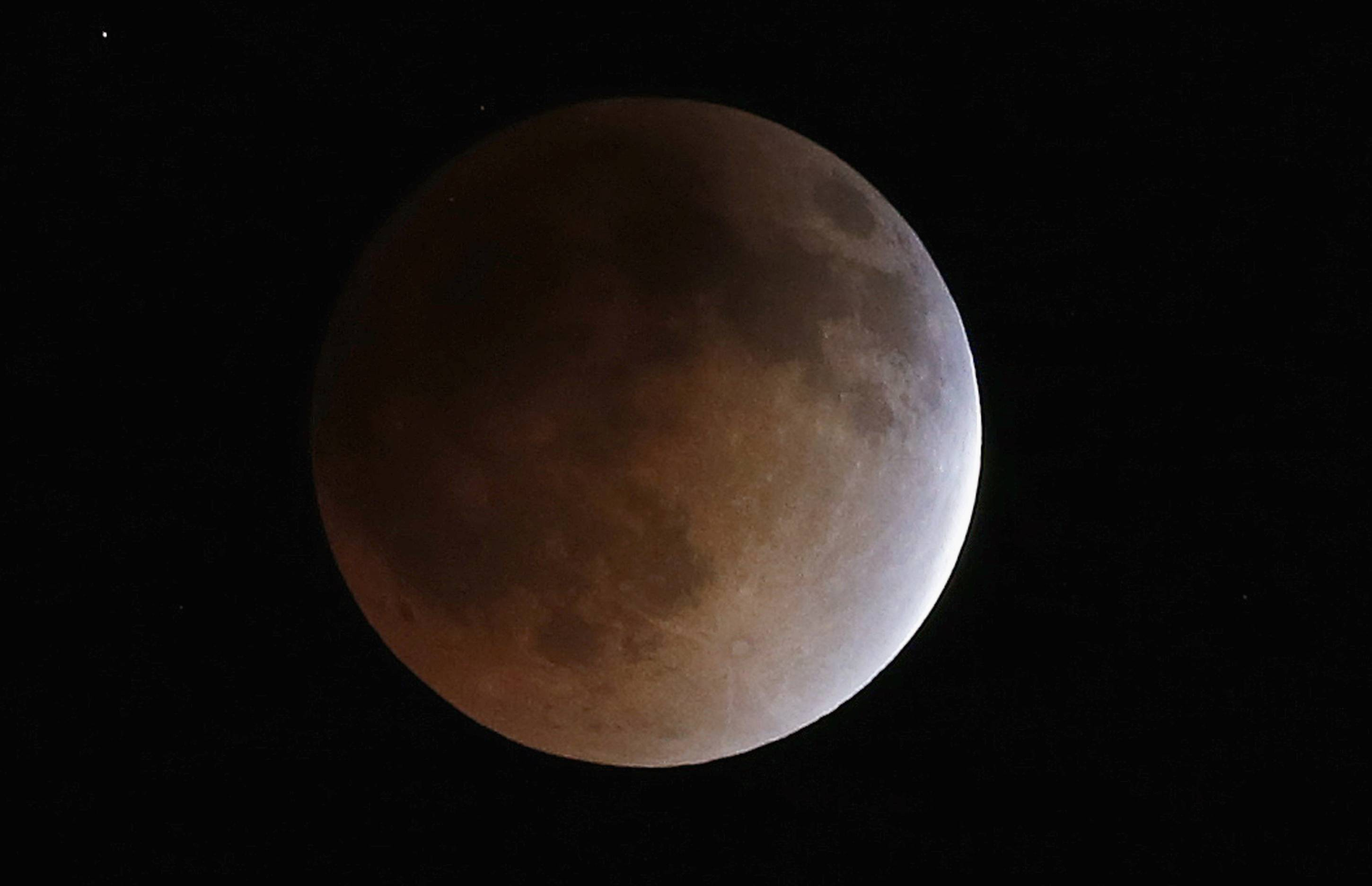 The moon turns an orange hue during a total lunar eclipse on Tuesday, April 15, 2014, in the sky above Phoenix. On April 29, the Southern Hemisphere will be treated to a type of solar eclipse. In all, four eclipses will occur this year, two lunar and two solar.