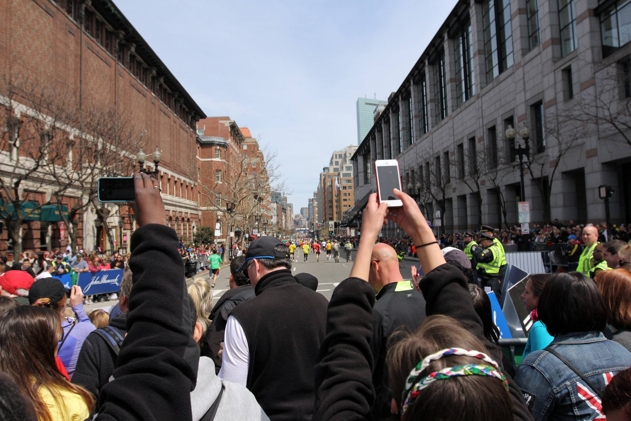 Spectators near the finish line take photos with camera phones just before two bombs exploded at the Boston Marathon on April 15, 2013. Many runners say they're eager to return to the race this year.