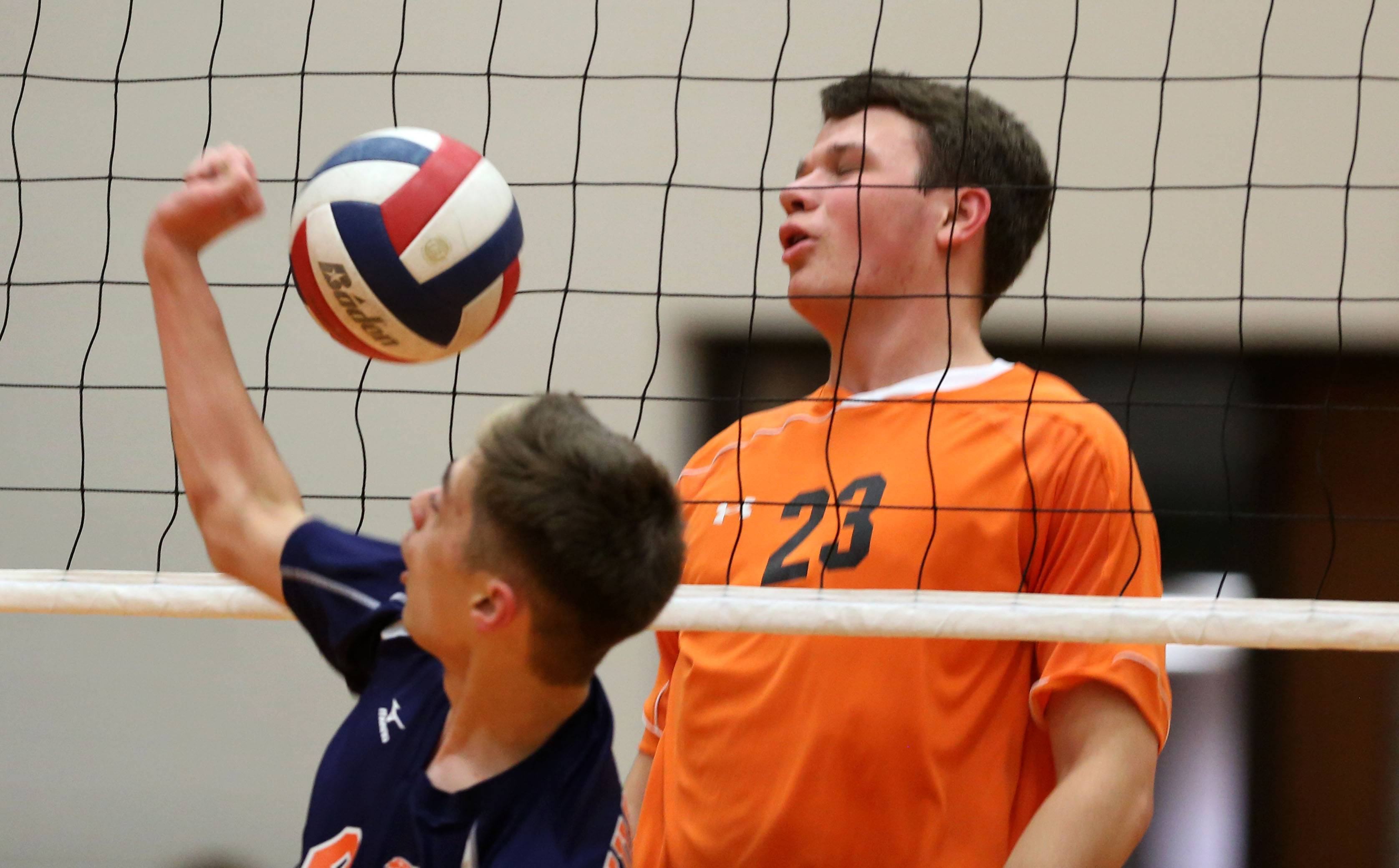 Naperville North's Jack Rothmund, left, battles Wheaton Warrenville South's Jerry Loar, right, during boys volleyball action.