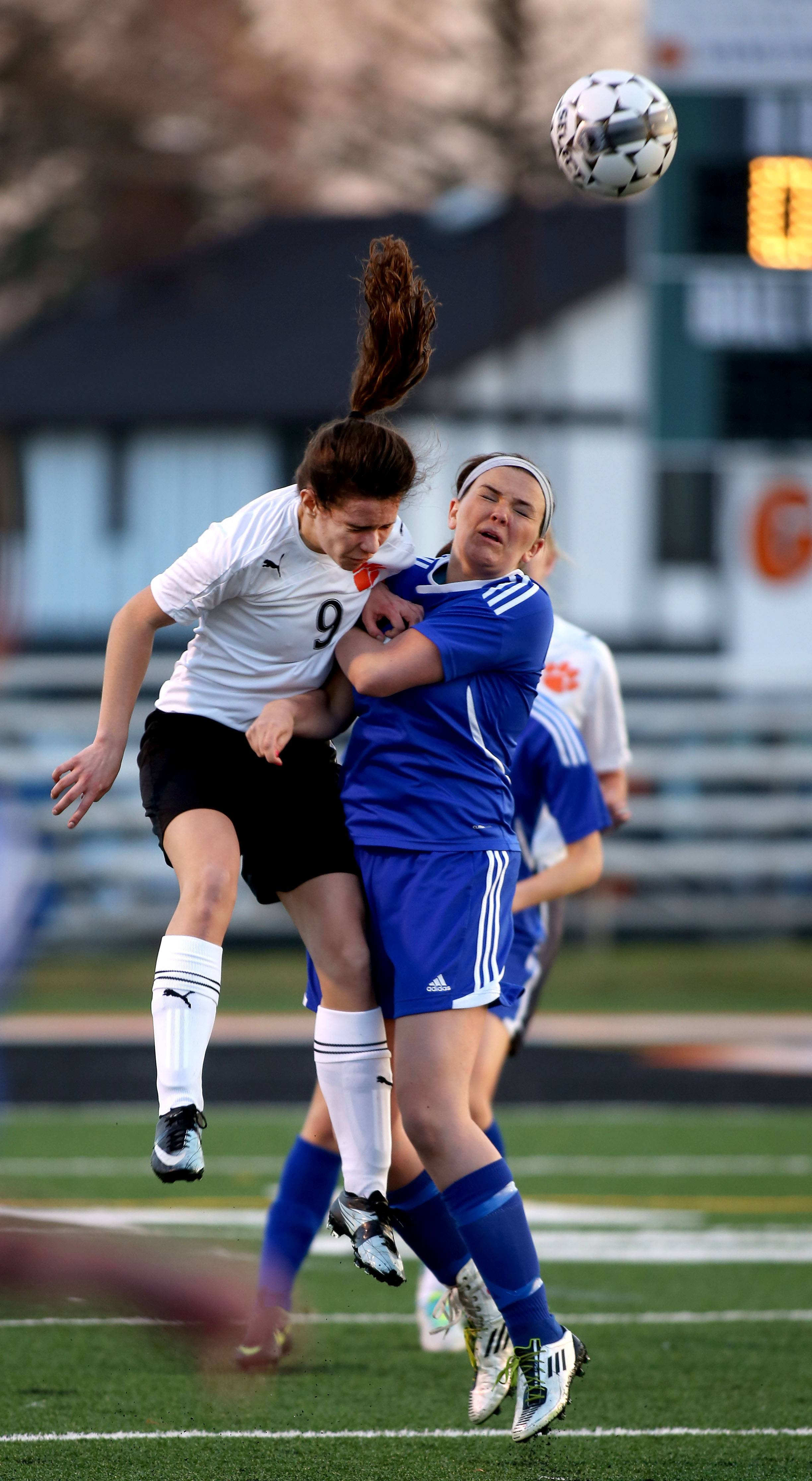Wheaton Warrenville South's Tori Adomshick, left, heads the ball away from Wheaton North's Madelyn Stubits during Tuesday's soccer match.