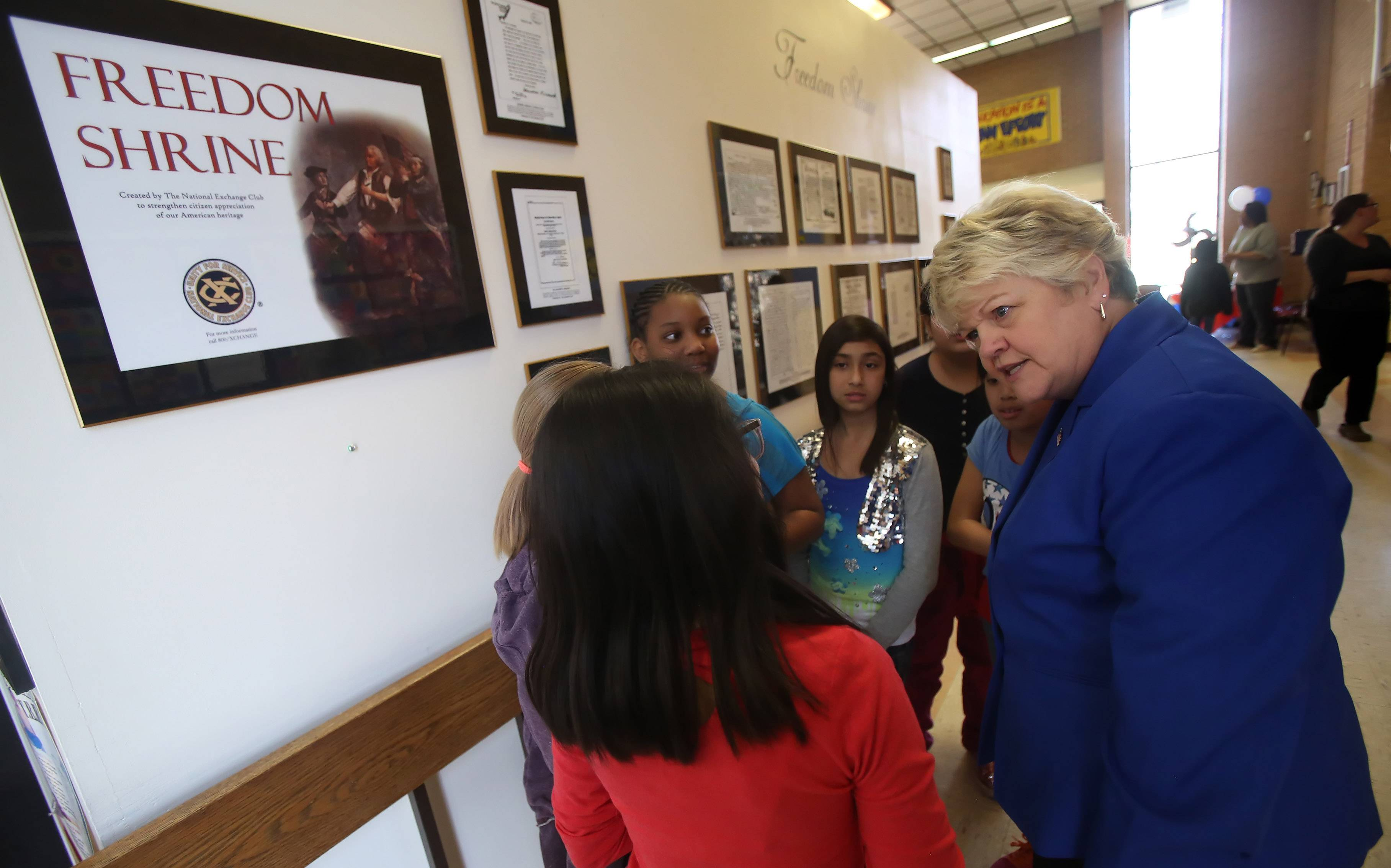 Round Lake Area Exchange Club member Judy Armstrong talks to W.J. Murphy students about the replicas of historic documents featured in the Freedom Shrine dedicated Wednesday at the Round Lake Park school.