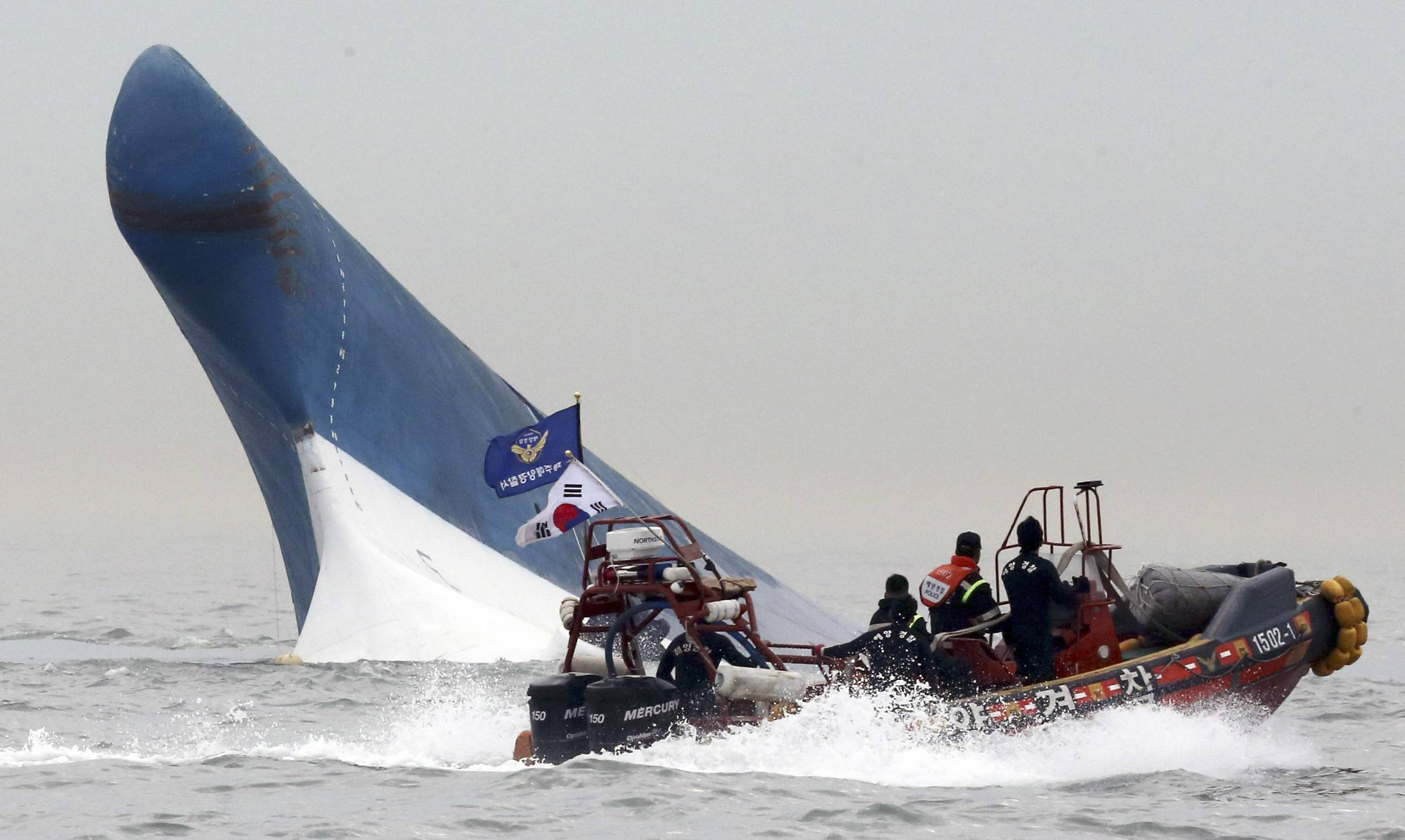 South Korean coast guard officers try to rescue passengers from a ferry sinking in the water off the southern coast near Jindo, south of Seoul, South Korea, Wednesday, April 16, 2014. The ferry carrying 459 people, mostly high school students on an overnight trip to a tourist island, sank off South Korea's southern coast on Wednesday, leaving nearly 300 people missing despite a frantic, hourslong rescue by dozens of ships and helicopters. At least four people were confirmed dead and 55 injured.