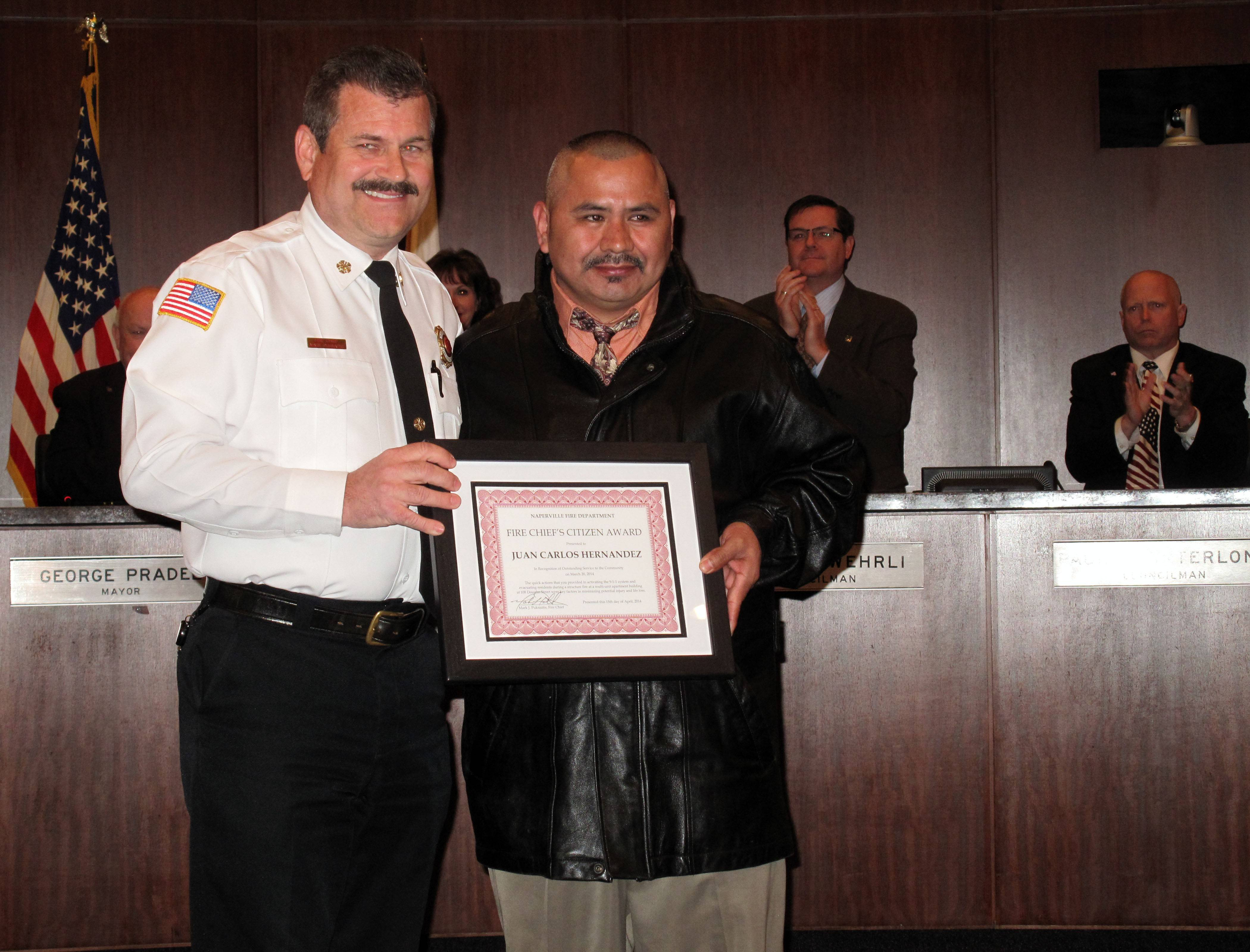 Juan Carlos Hernandez, 39, of Naperville, receives the Fire Chief's Award from Naperville Chief Mark Puknaitis for his efforts to help evacuate residents of an apartment building that caught fire March 20.