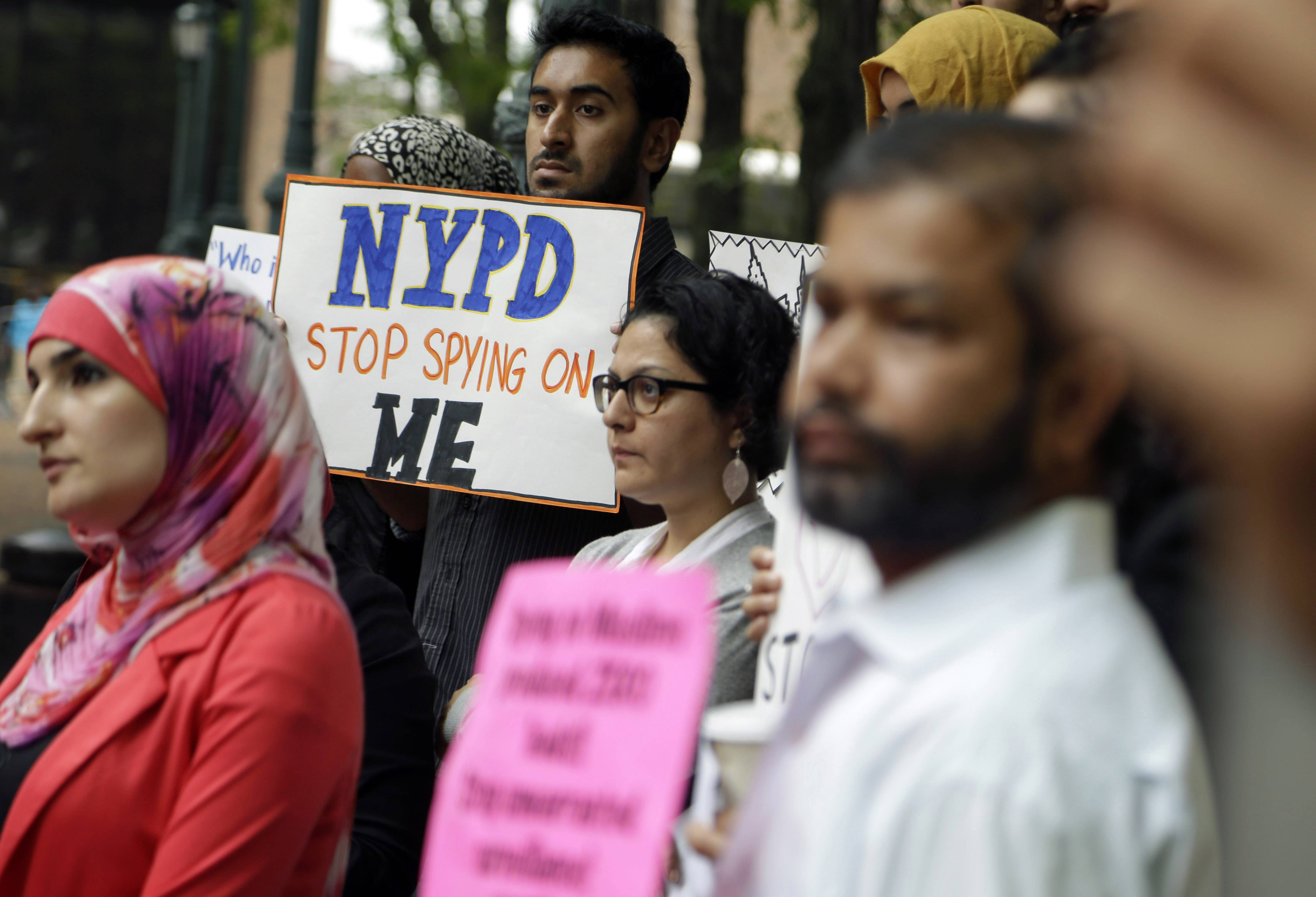 A group of people hold signs protesting the New York Police Department's program of infiltrating and informing on Muslim communities during a rally near police headquarters in New York. The NYPD confirmed Tuesday it disbanded the special intelligence unit that monitored Muslim communities in New York and New Jersey.