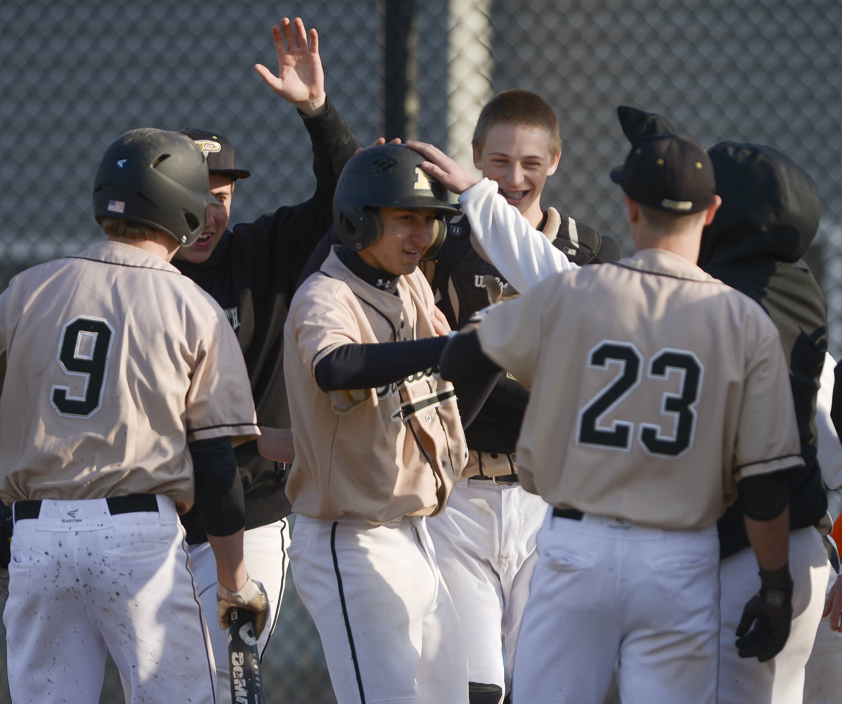 Glenbard North's Jim Krippinger is congratulated by his teammates after hit a home run during his team's 6-0 win over Naperville North at home Wednesday.
