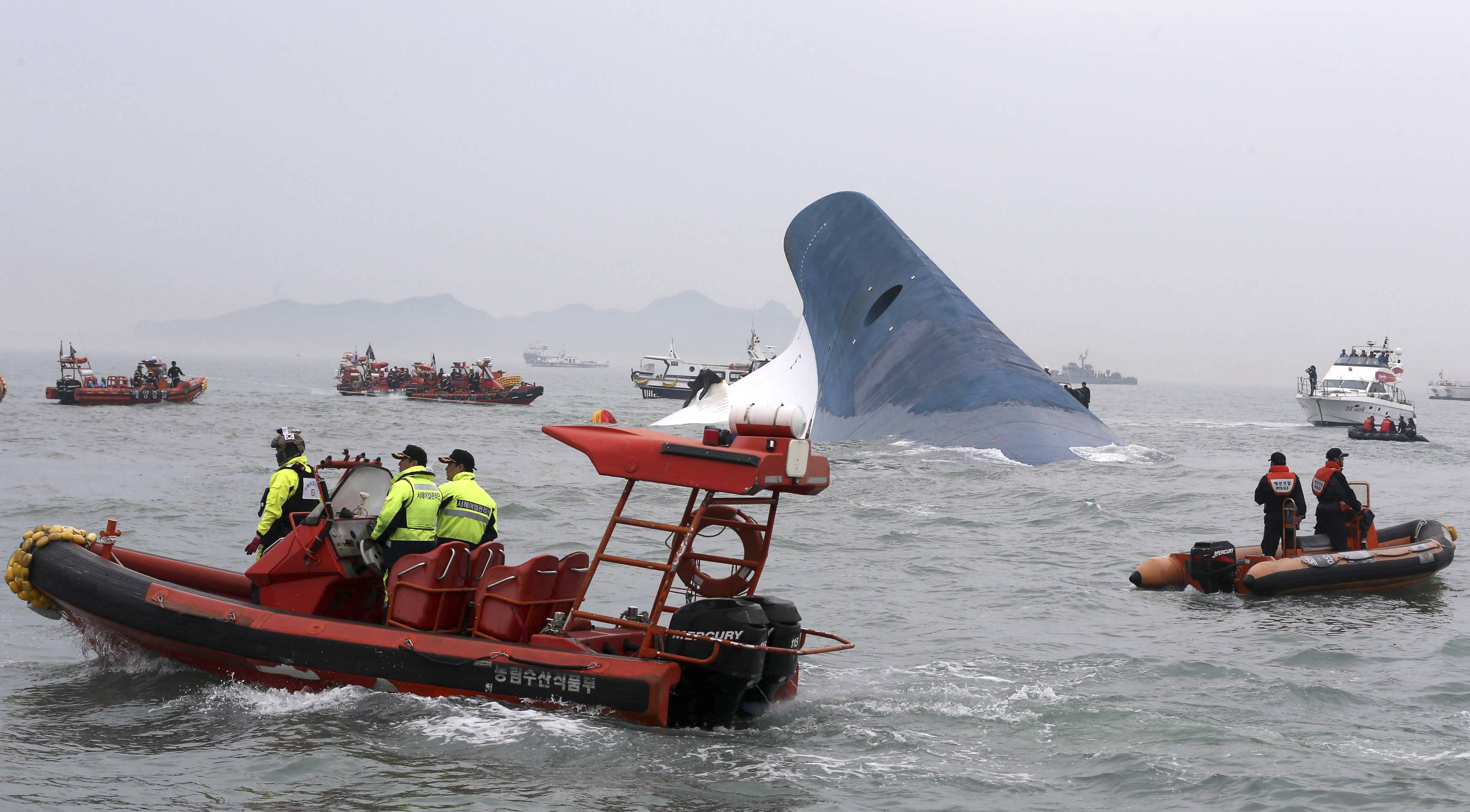 South Korean coast guard officers and rescue team members try to rescue passengers from the ferry Sewol in the water off the southern coast near Jindo, south of Seoul, Wednesday, April 16, 2014. Dozens of boats, helicopters and divers scrambled Wednesday to rescue more than 470 people, including 325 high school students on a school trip, after a ferry sank off South Korea's southern coast.
