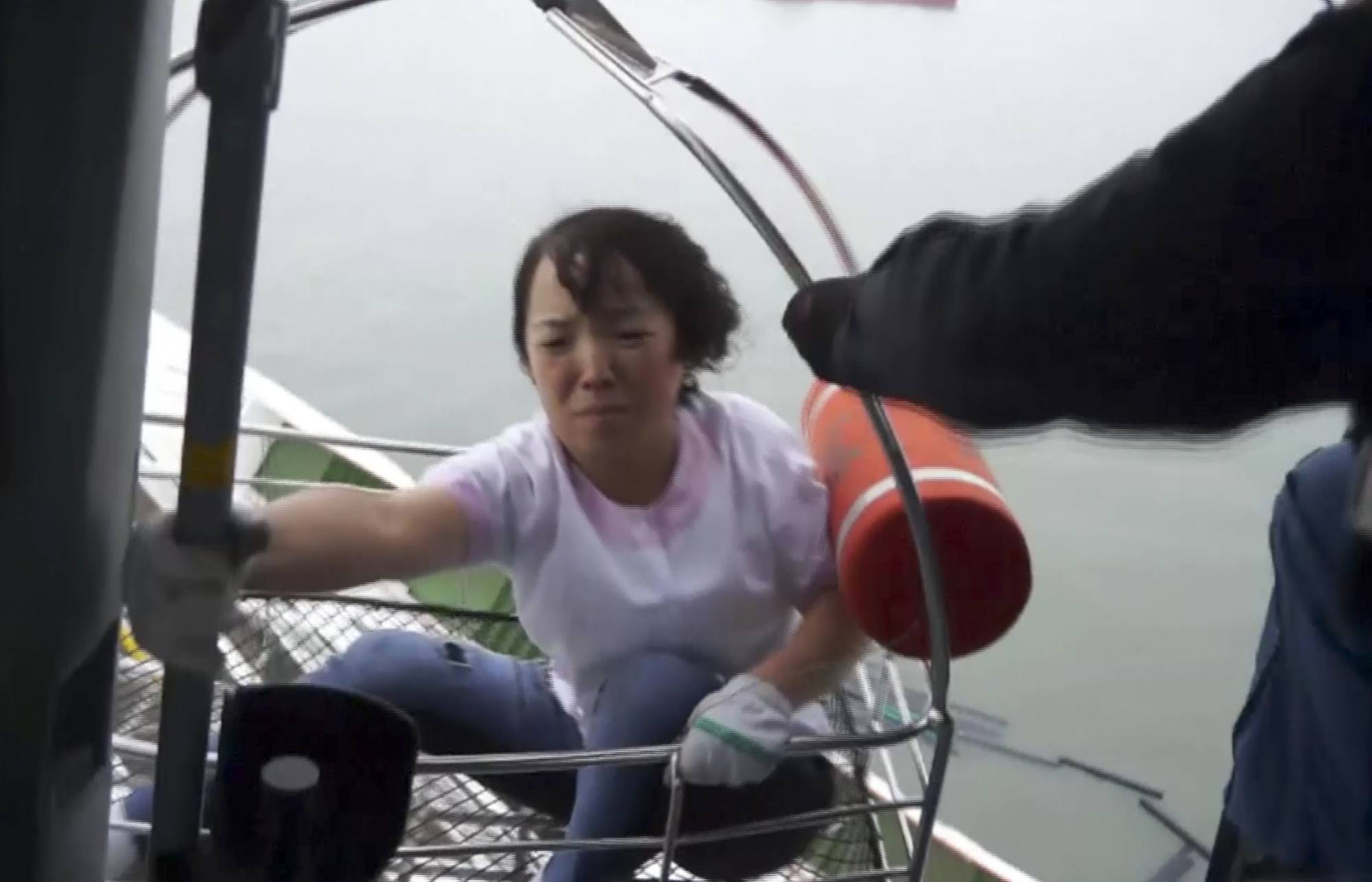 In this image made from video from South Korean Coast Guard, a passenger of a ferry sinking off South Korea's southern coast is rescued and hoisted onto a Coast Guard helicopter off the southern coast near Jindo, south of Seoul, Wednesday, April 16, 2014. Nearly 300 people were still missing Wednesday several hours after a ferry carrying 459, most of them high school students, sank in cold waters off South Korea's southern coast.