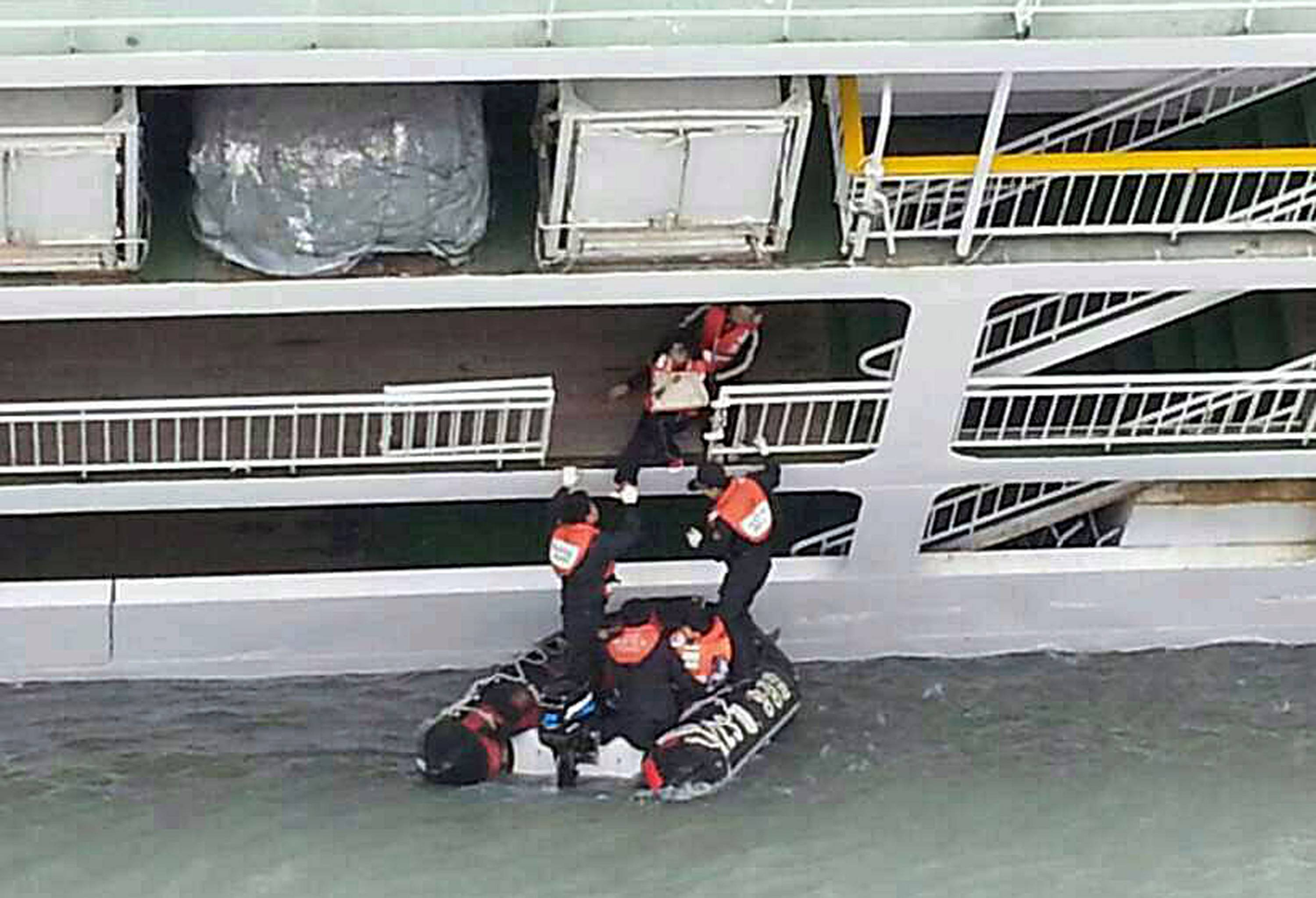 In this photo released by the South Korean Coast Guard via Yonhap News Agency, South Korean coast guard officers rescue passengers from a sinking ferry off the southern coast near Jindo, south of Seoul, South Korea, Wednesday, April 16, 2014. A ferry carrying 459 people, mostly high school students on an overnight trip to a tourist island, sank off South Korea's southern coast on Wednesday, leaving nearly 300 people missing despite a frantic, hourslong rescue by dozens of ships and helicopters.