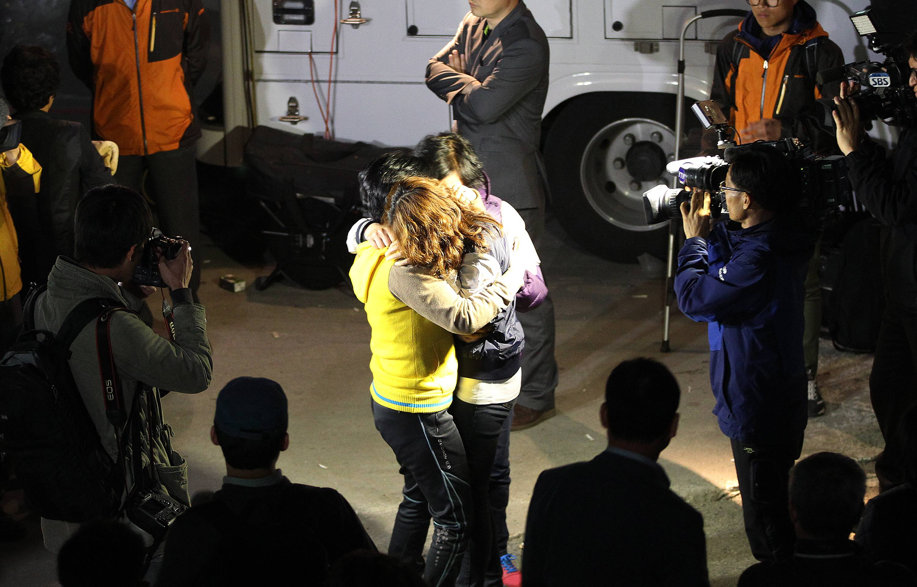 Relatives hug each other as they wait for missing people at a port in Jindo, South Korea, Wednesday, April 16, 2014. A South Korean passenger ship carrying more than 470 people, including many high school students, sunk off the country's southern coast Wednesday after sending a distress call, officials said.