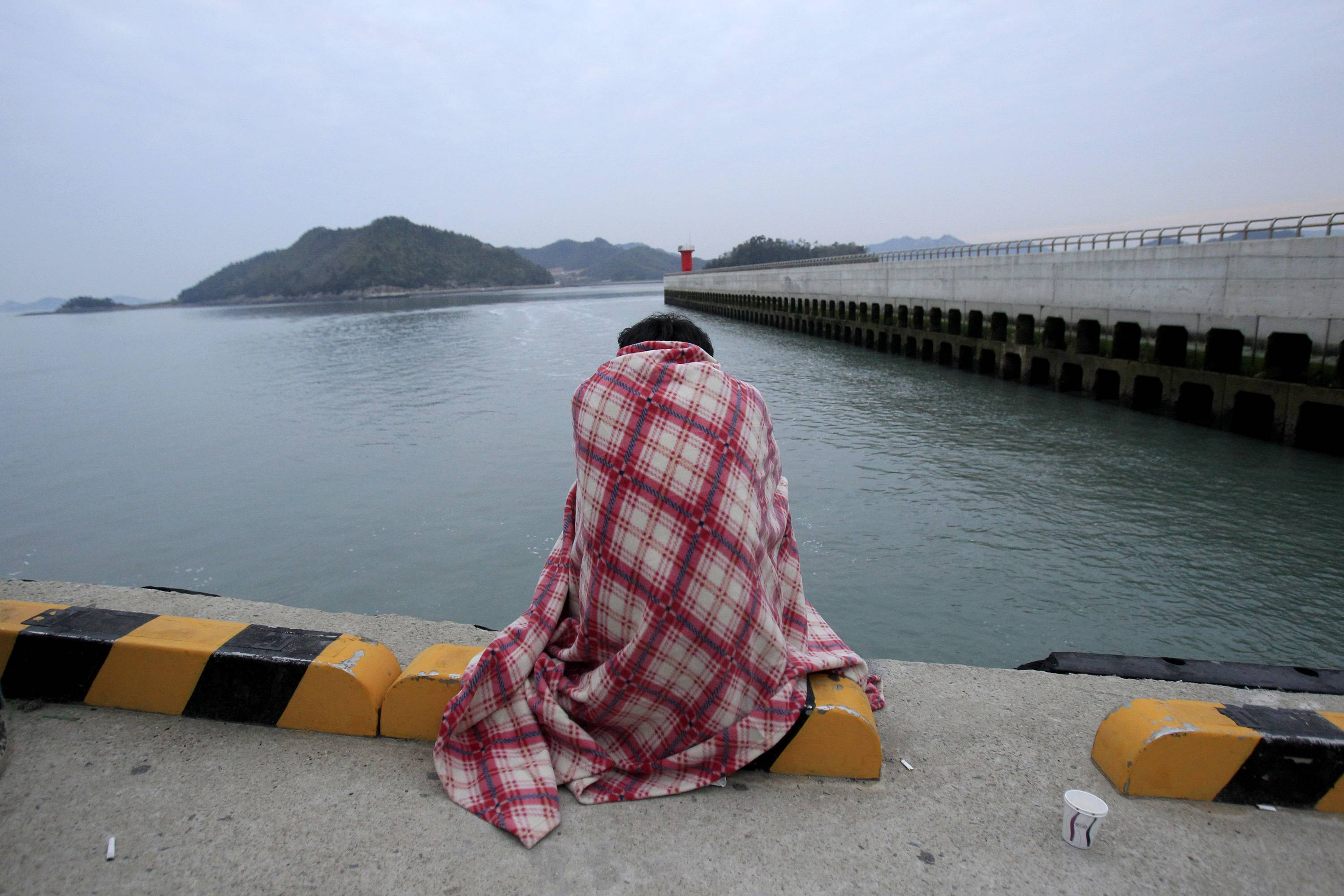 A relative waits for their missing loved one at a port in Jindo, South Korea, Wednesday, April 16, 2014. A ferry carrying 459 people, mostly high school students on an overnight trip to a tourist island, sank off South Korea's southern coast on Wednesday, leaving nearly 300 people missing despite a frantic, hourslong rescue by dozens of ships and helicopters.