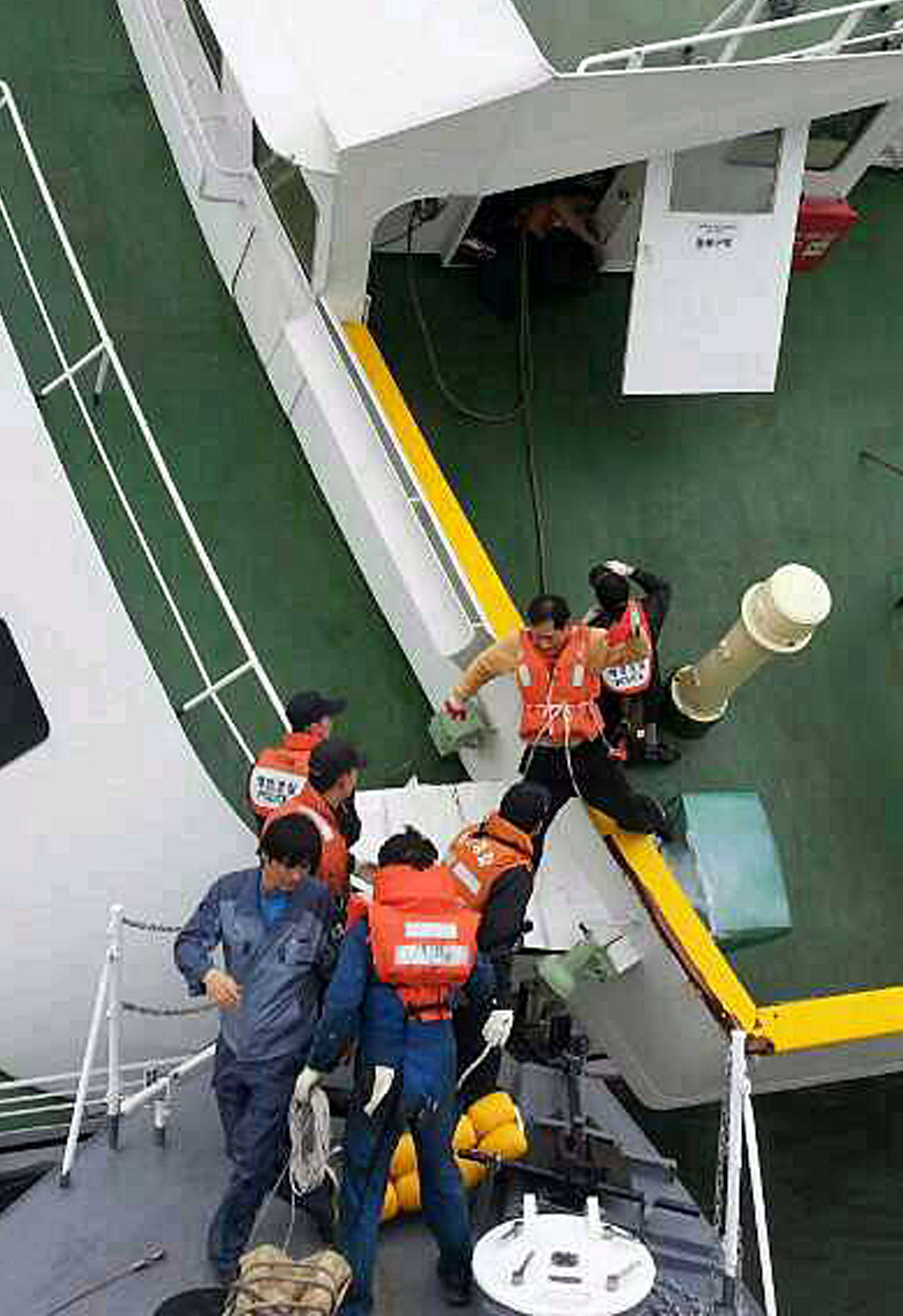 In this photo released by South Korea Coast Guard via Yonhap News Agency, South Korean coast guard rescue passengers from a ferry in the water off the southern coast near Jindo, South Korea, Wednesday, April 16, 2014. The ferry carrying 459 people, mostly high school students on an overnight trip to a tourist island, sank off South Korea's southern coast on Wednesday, leaving nearly 300 people missing despite a frantic, hourslong rescue by dozens of ships and helicopters.