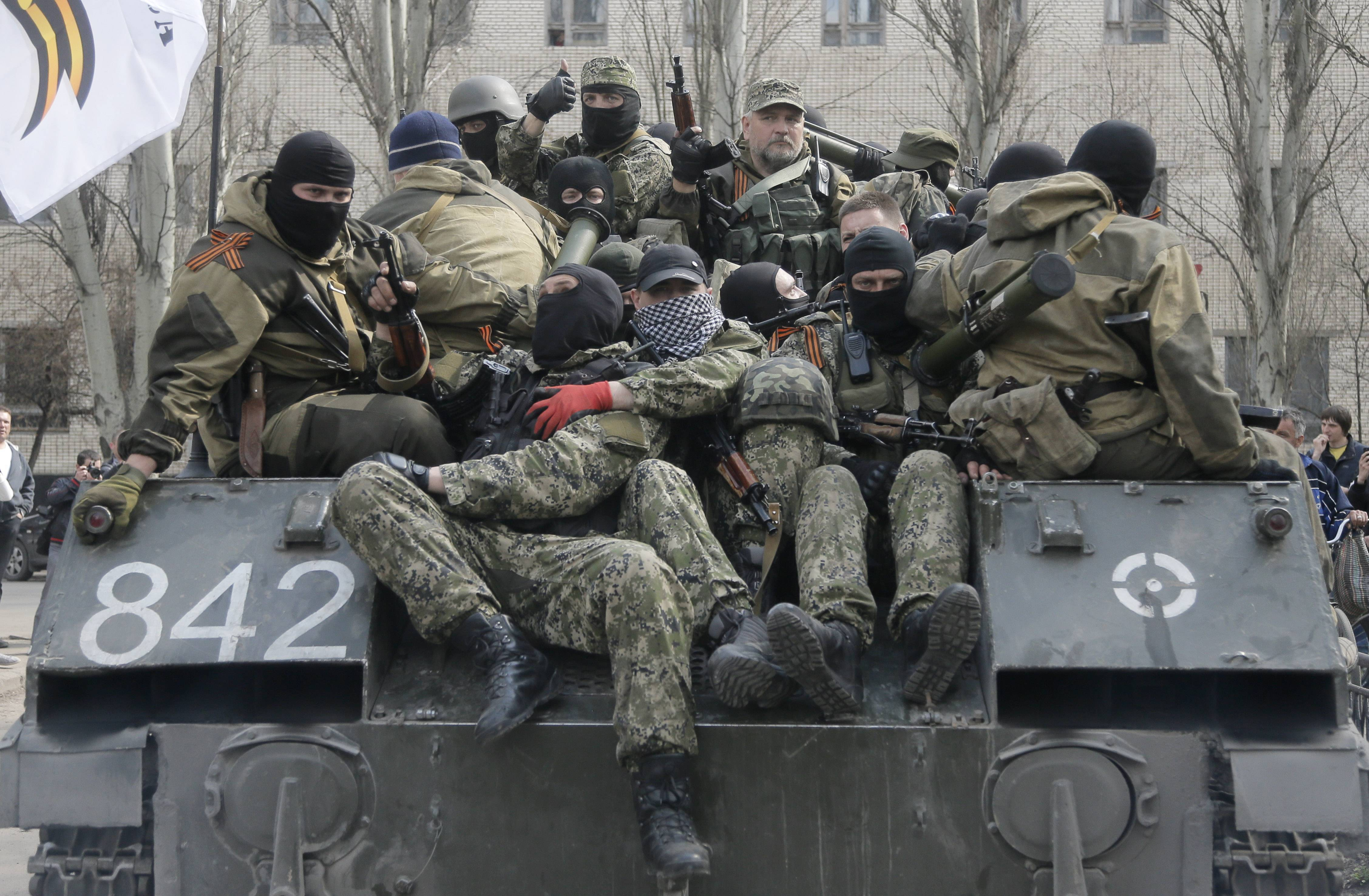 A combat vehicle with pro-Russian gunman on top runs Wednesday through downtown Slovyansk. The troops on those vehicles wore green camouflage uniforms, had automatic weapons and grenade launchers and at least one had the St. George ribbon attached to his uniform, which has become a symbol of the pro-Russian insurgency in eastern Ukraine.