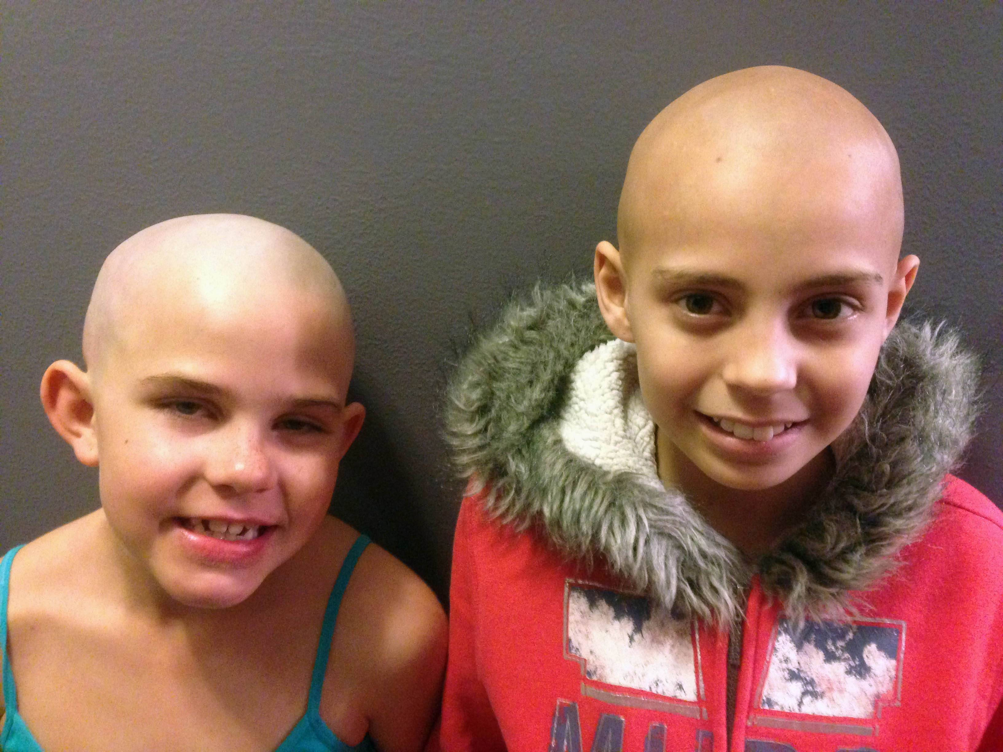 Kamryn Renfro, 9, left, and Delaney Clements, 11, right, stand together for a photo in Grand Junction, Colo., shortly after Kamryn had her head shaved to support Delaney, who lost her hair after treatment for cancer. Kamryn was suspended from her public charter school in Grand Junction because a shaved head goes against the school's dress code. But the school quickly reversed the decision.