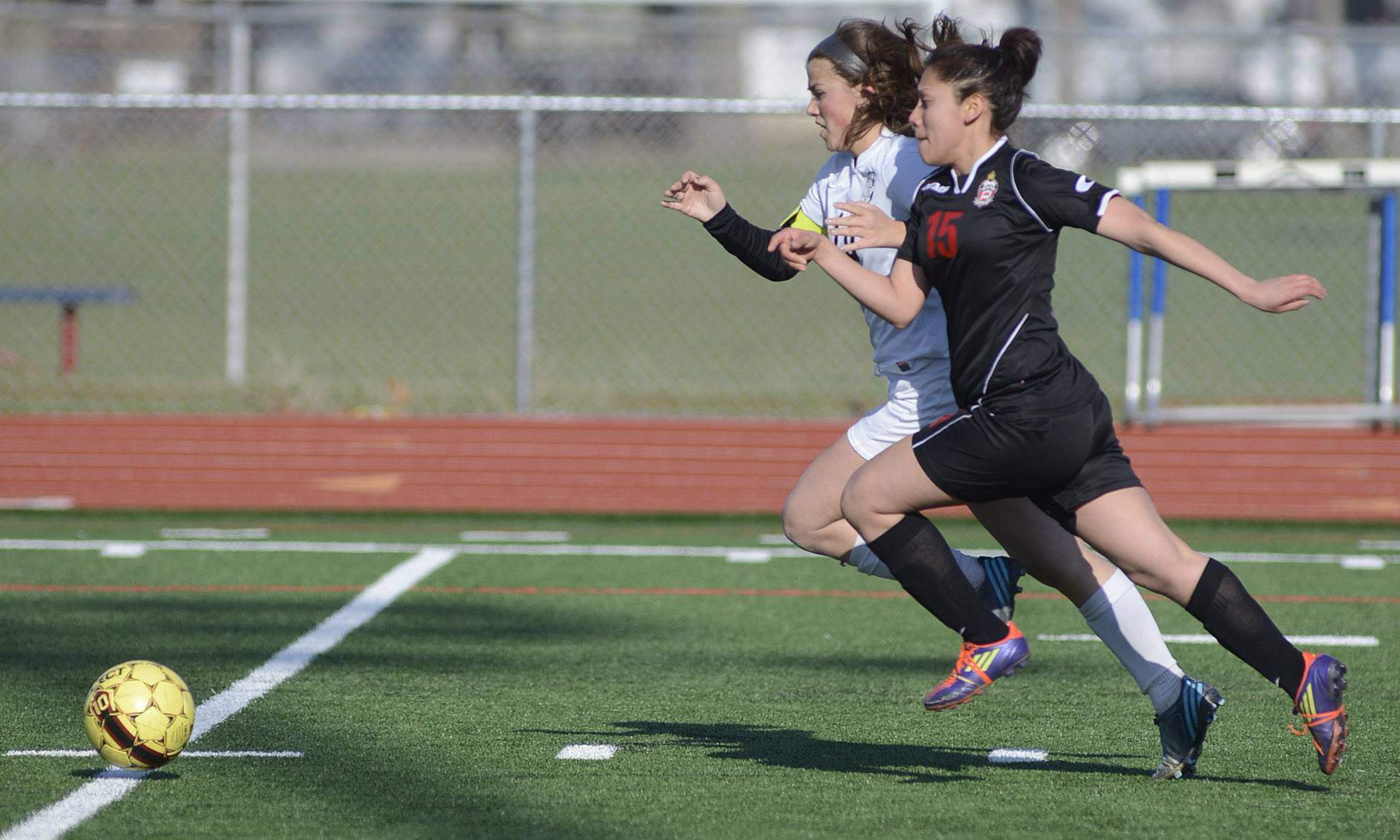 Kaneland's Michelle Ortiz and East Aurora's Jacqueline Palestina dash for the ball in the first half on Wednesday, April 16.