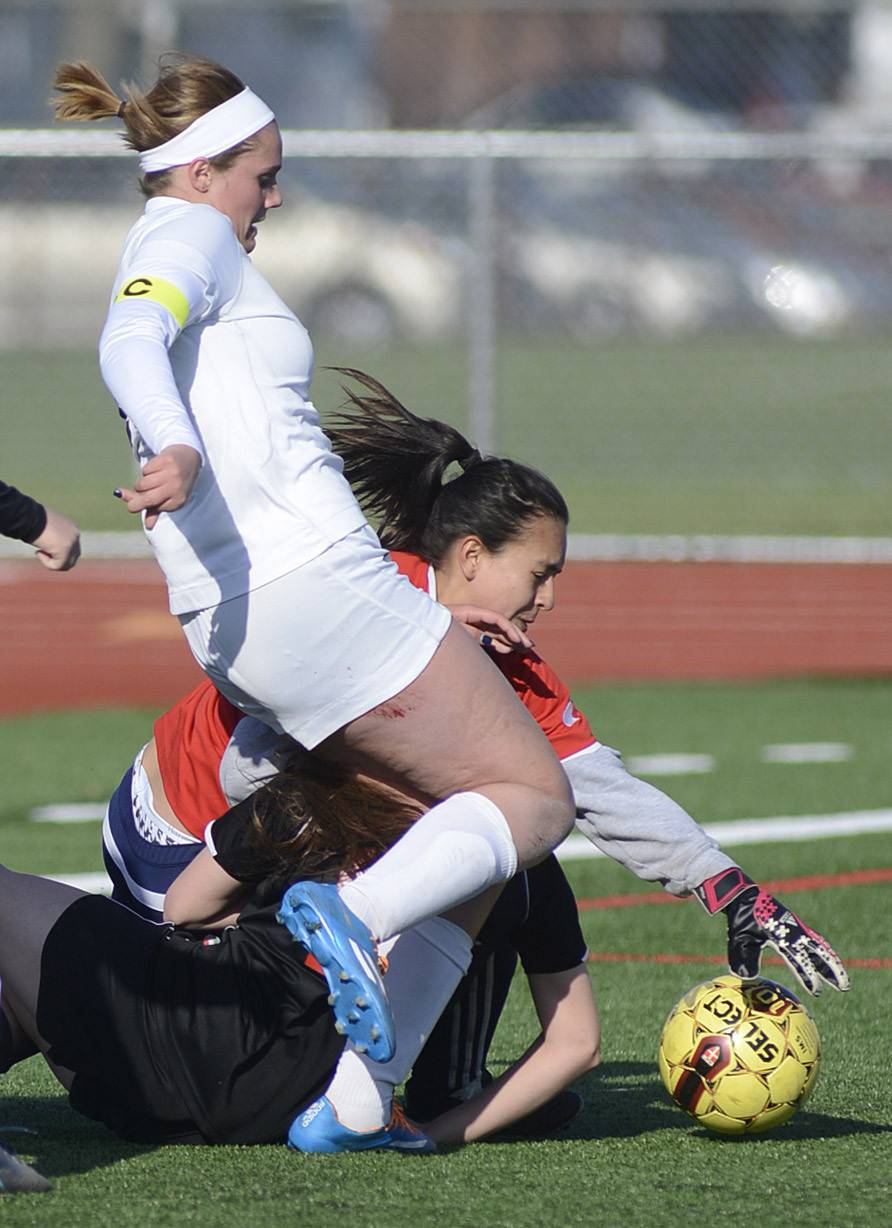 Kaneland's Delaney Stryczek, East Aurora's Rita Oceguera, and East Aurora's goalie Ruby Garcia collide while all battling for the ball near the goal in the first half on Wednesday, April 16.