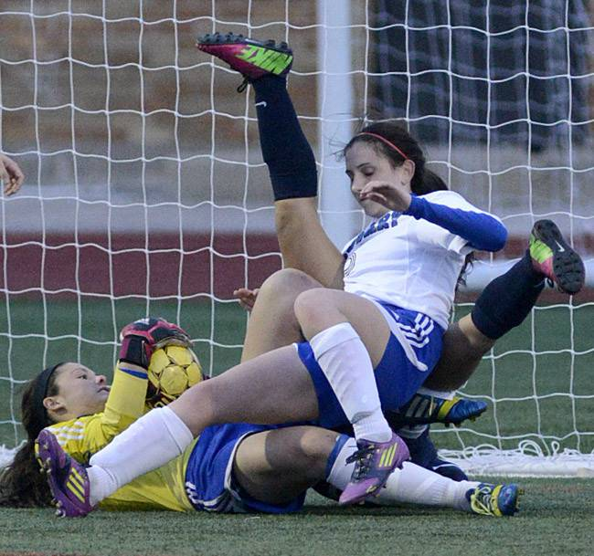 Rosary goalie Lauren Frasca hangs onto the ball while teammate Cassie Duck (facing) gets jumbled up in the legs of West Aurora's Cristina Sosa in the second half on Wednesday, April 16.