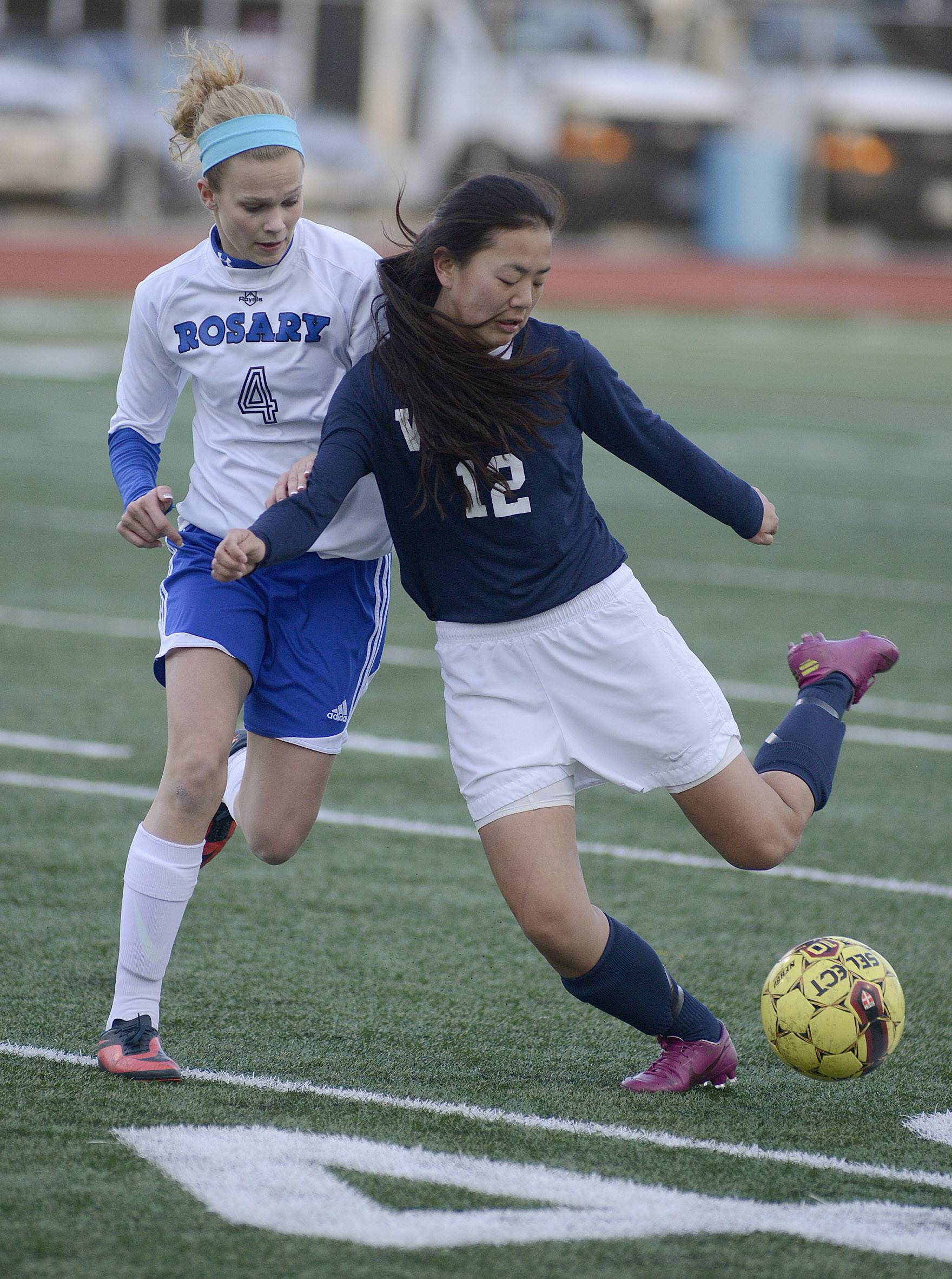 Rosary's Quincy Kellett, left, and West Aurora's Carli Hix fight for the ball in the first half on Wednesday, April 16.