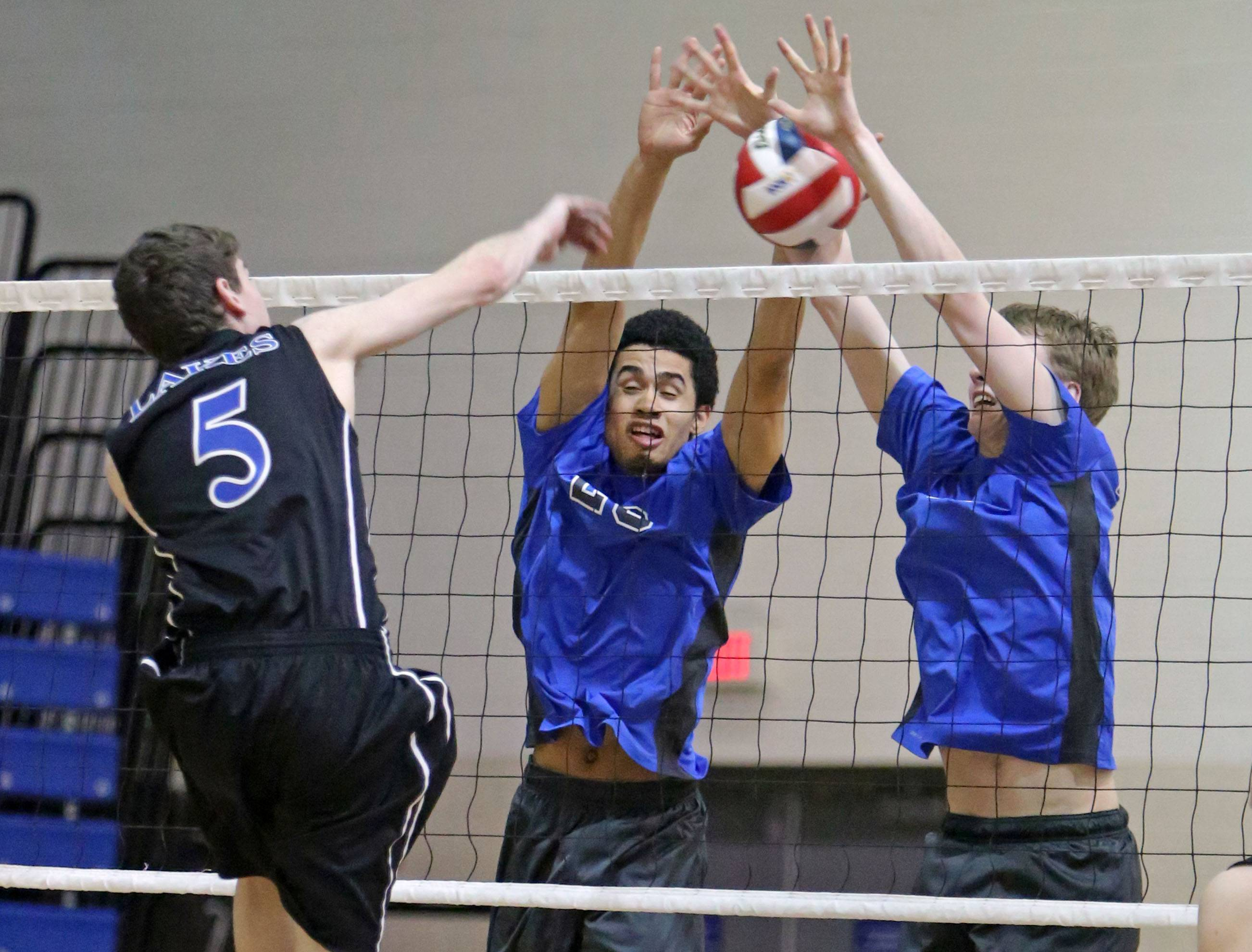 Lakes' Nick Halberg, left, spikes one at Vernon Hills' Lem Turner and Tyler Small during their game Wednesday at Lakes.