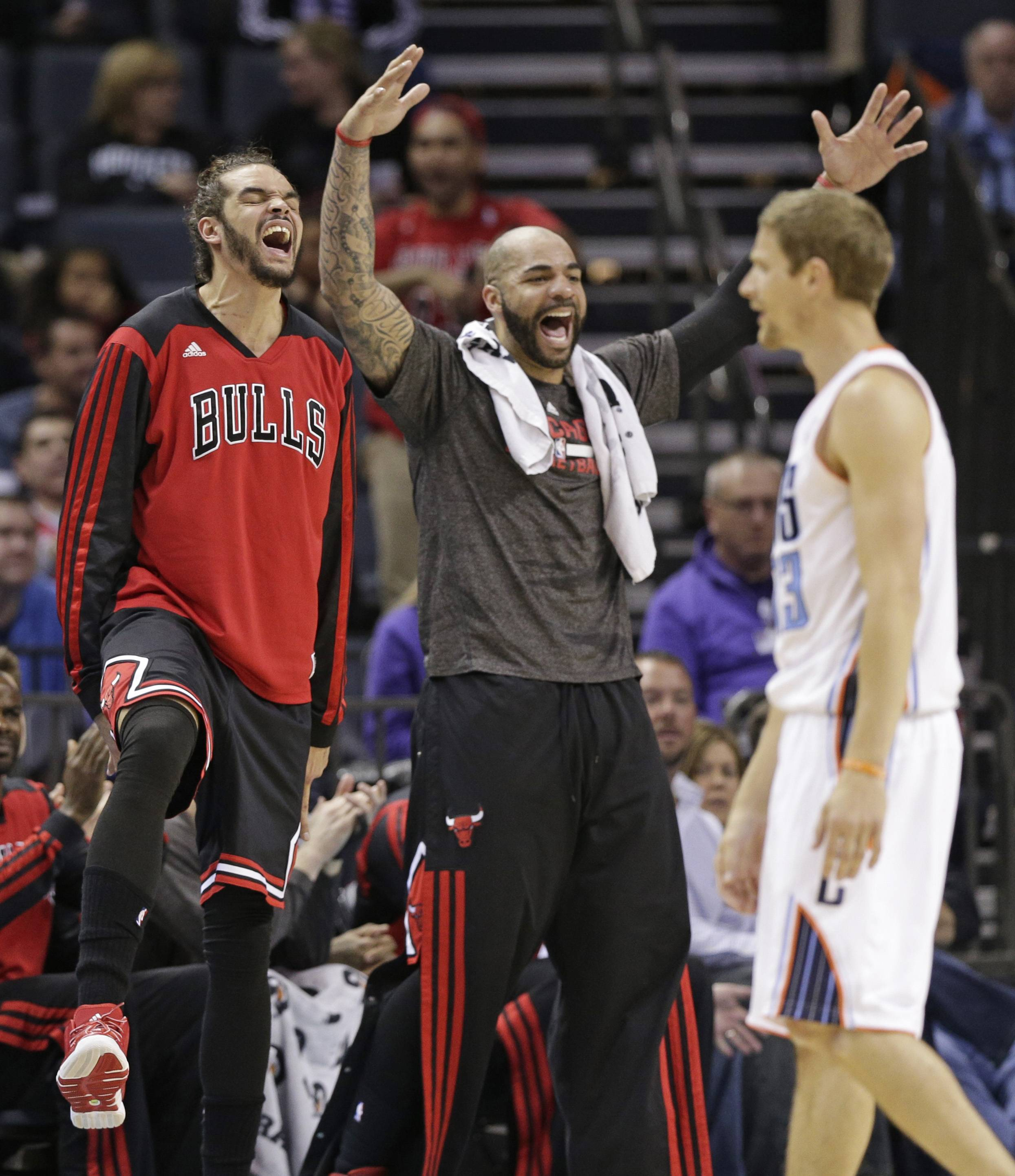 The Bulls' Joakim Noah, left, and Carlos Boozer, center, react after Charlotte Bobcats' Luke Ridnour, right, was called for a foul during Wednesday night's game in Charlotte. The Bulls lost 91-86 in overtime, and they'll play either Brooklyn or Washington in the first playoffs round.