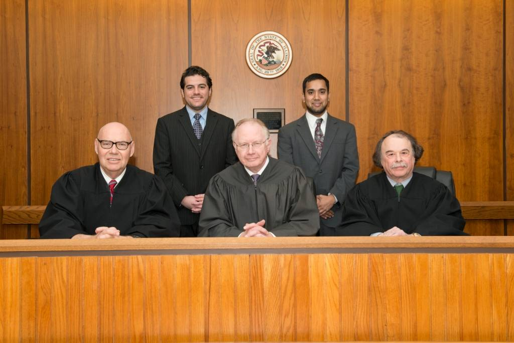 The 2014 NIU Law Moot Court champion team of second-year law students (standing from left) Nick Perrone and Jesse Guth argued before the distinguished bench of (seated from left): Judge James F. Holderman, U.S. District Court, Northern District of Illinois; Justice Thomas L. Kilbride, Illinois Supreme Court; and professor Barry Sullivan, Loyola University School of Law.