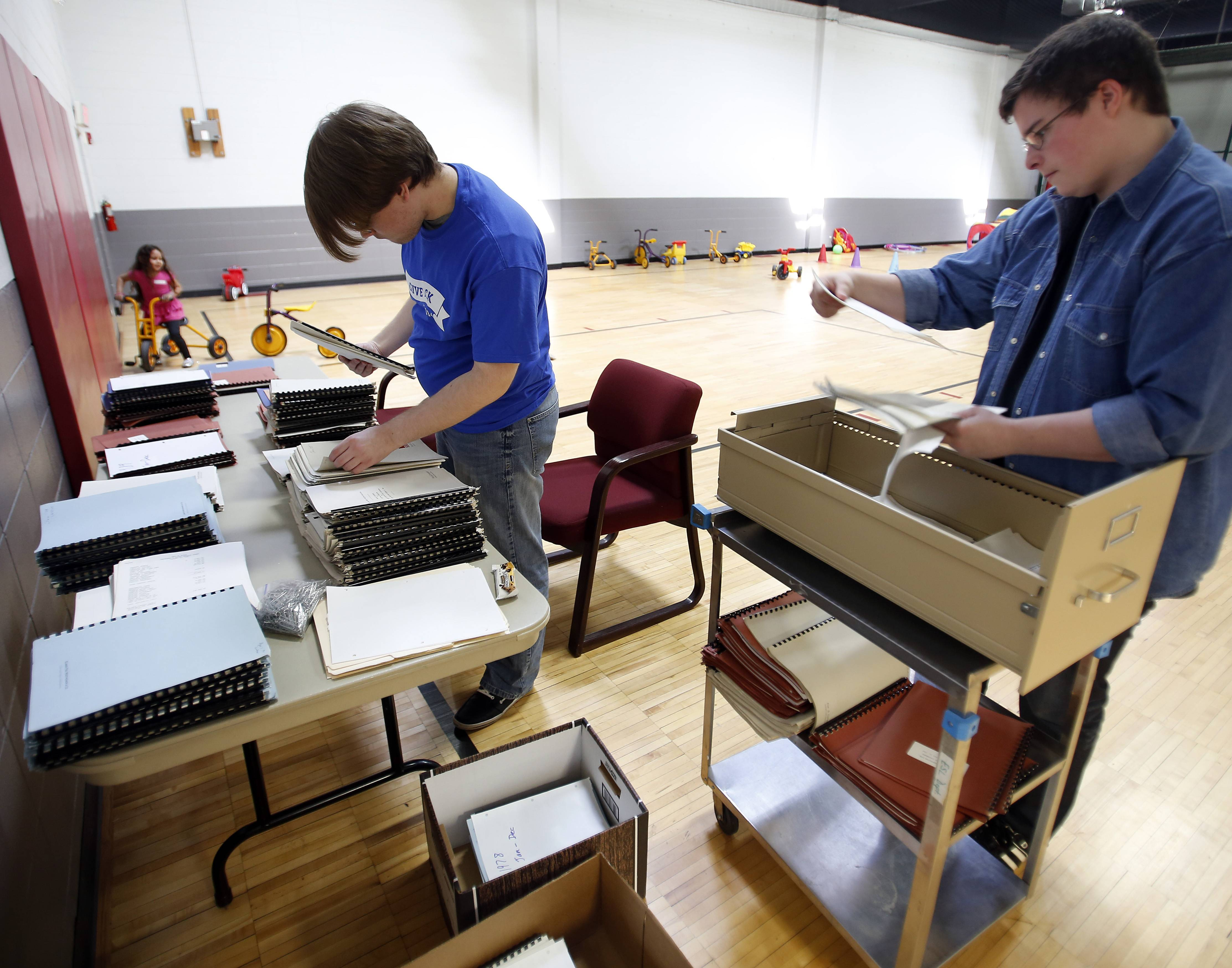 Student David Loske, 16, and Tim Daugaard, 23, a volunteer chaperon, sort records to prepare them to be scanned Thursday at the Elgin YWCA. They were part of a group from Westminster Christian School in Elgin who were giving back to the community. More than 350 students, teachers, and volunteers worked at 20 locations during the second annual Give Back Day.