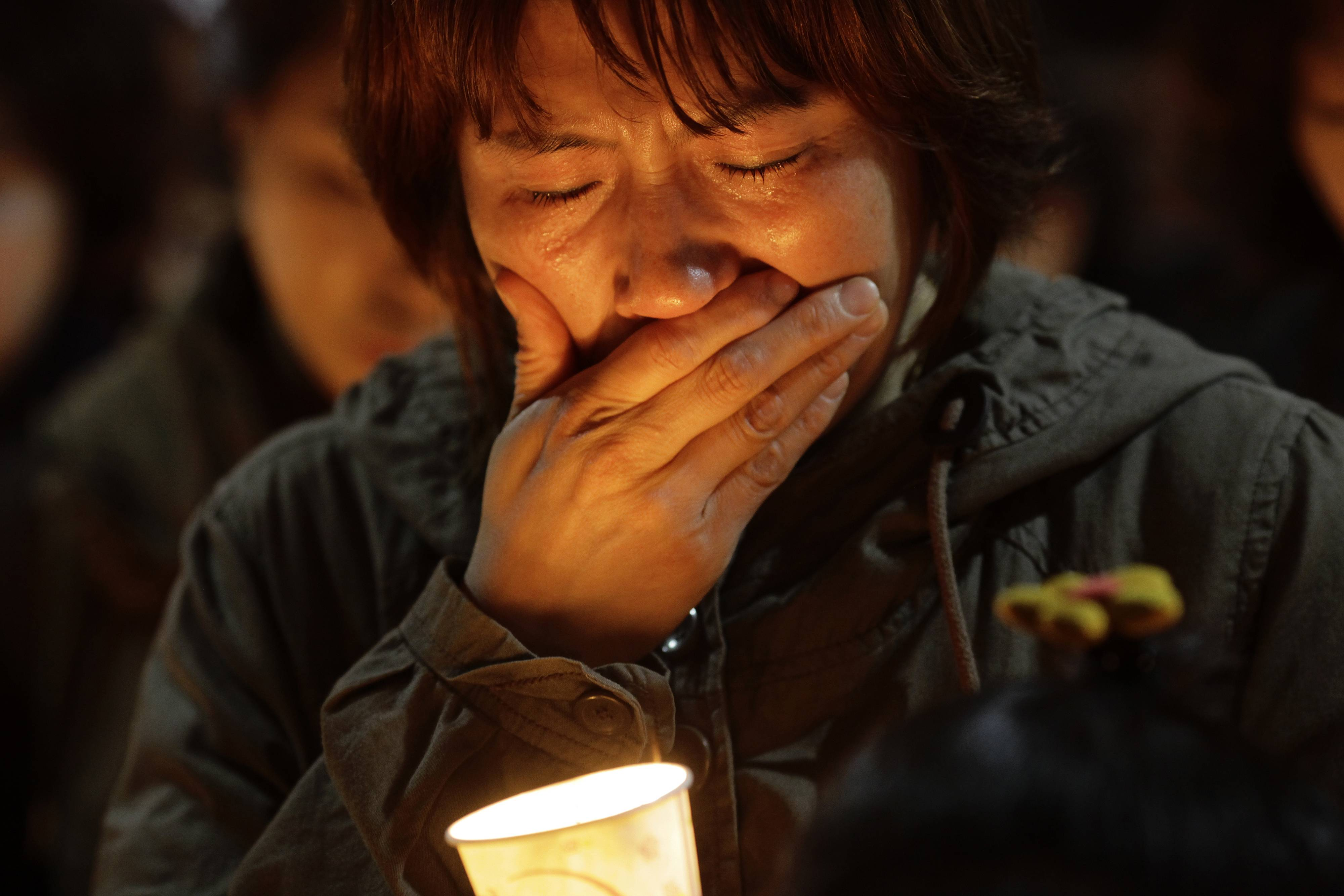 A woman offers prayer with candlelight for the missing passengers of a sunken ferry at Danwon High School in Ansan, South Korea, Thursday.