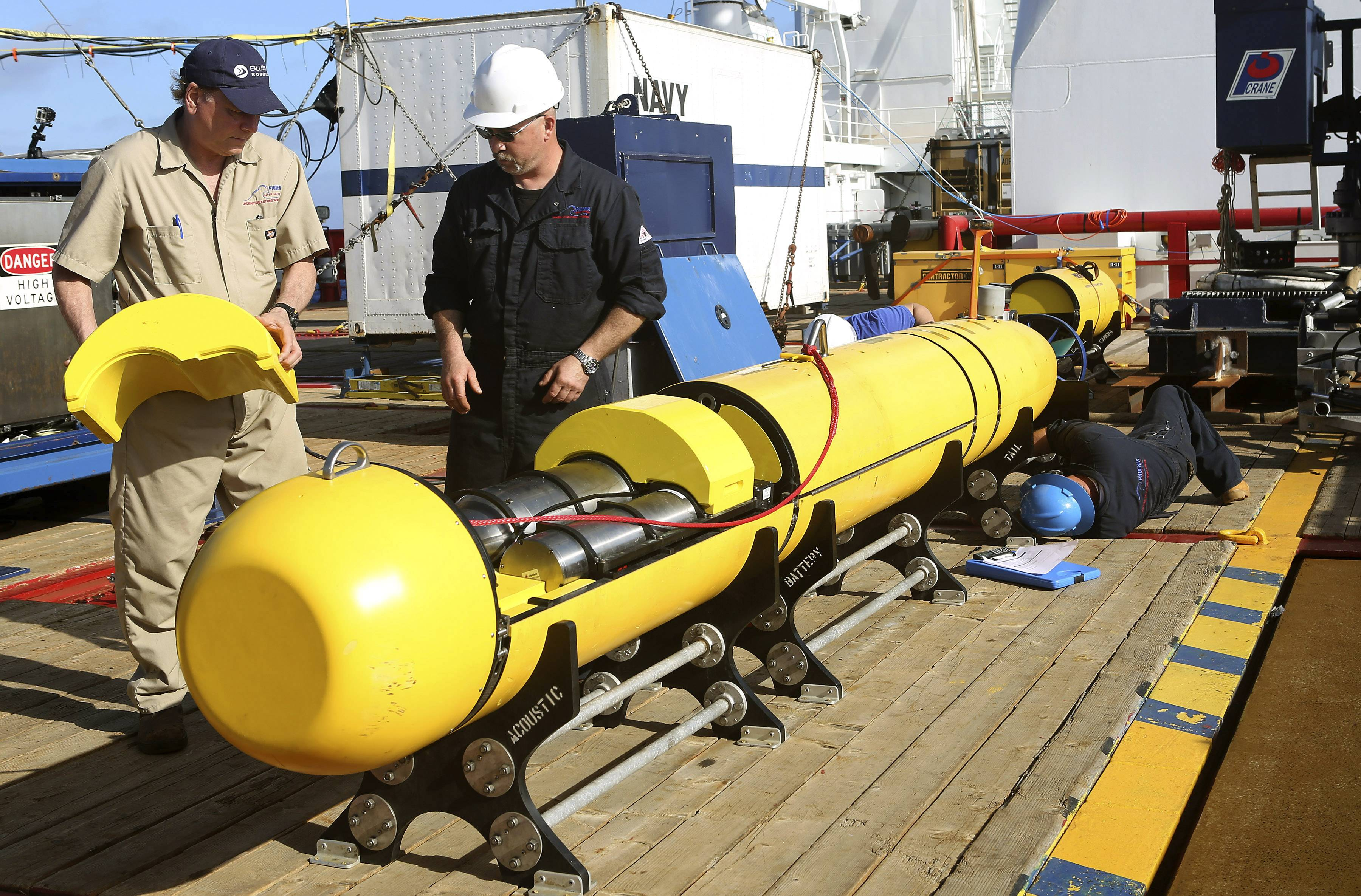 Phoenix International's Chris Minor, right, and Curt Newport inspect an autonomous underwater vehicle Monday before it is deployed from ADV Ocean Shield in the search of the missing Malaysia Airlines Flight 370 in the southern Indian Ocean. The search area for the missing Malaysian jet has proved too deep for the robotic submarine which was hauled back to the surface of the Indian Ocean less than half way through its first seabed hunt for wreckage and the all-important black boxes, authorities said on Tuesday.