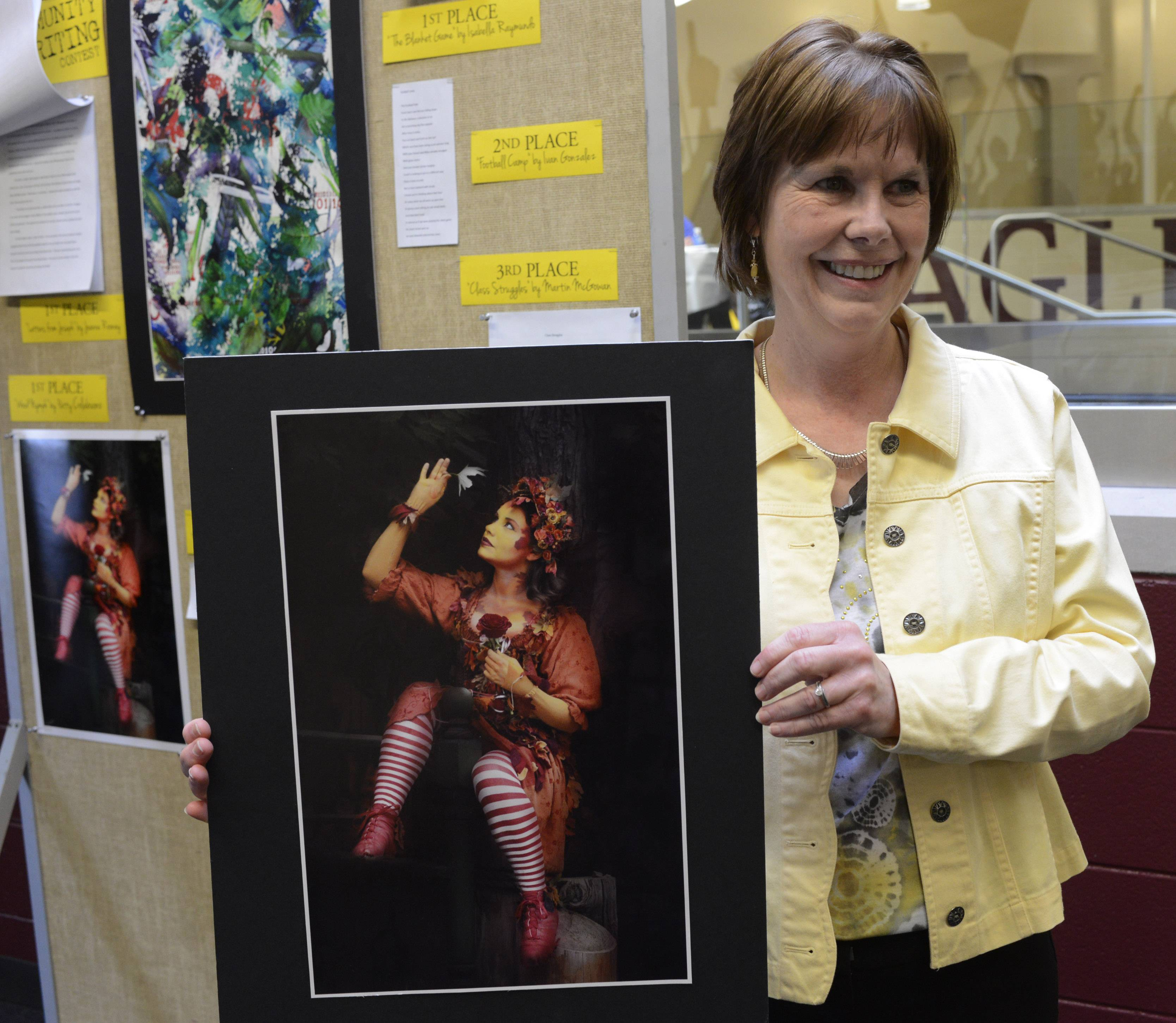 "First-place winner Patty Colabuono of Arlington Heights holds the original print of her photograph ""Wood Nymph"" during the annual Arts Unlimited reception and program Wednesday in Arlington Heights."