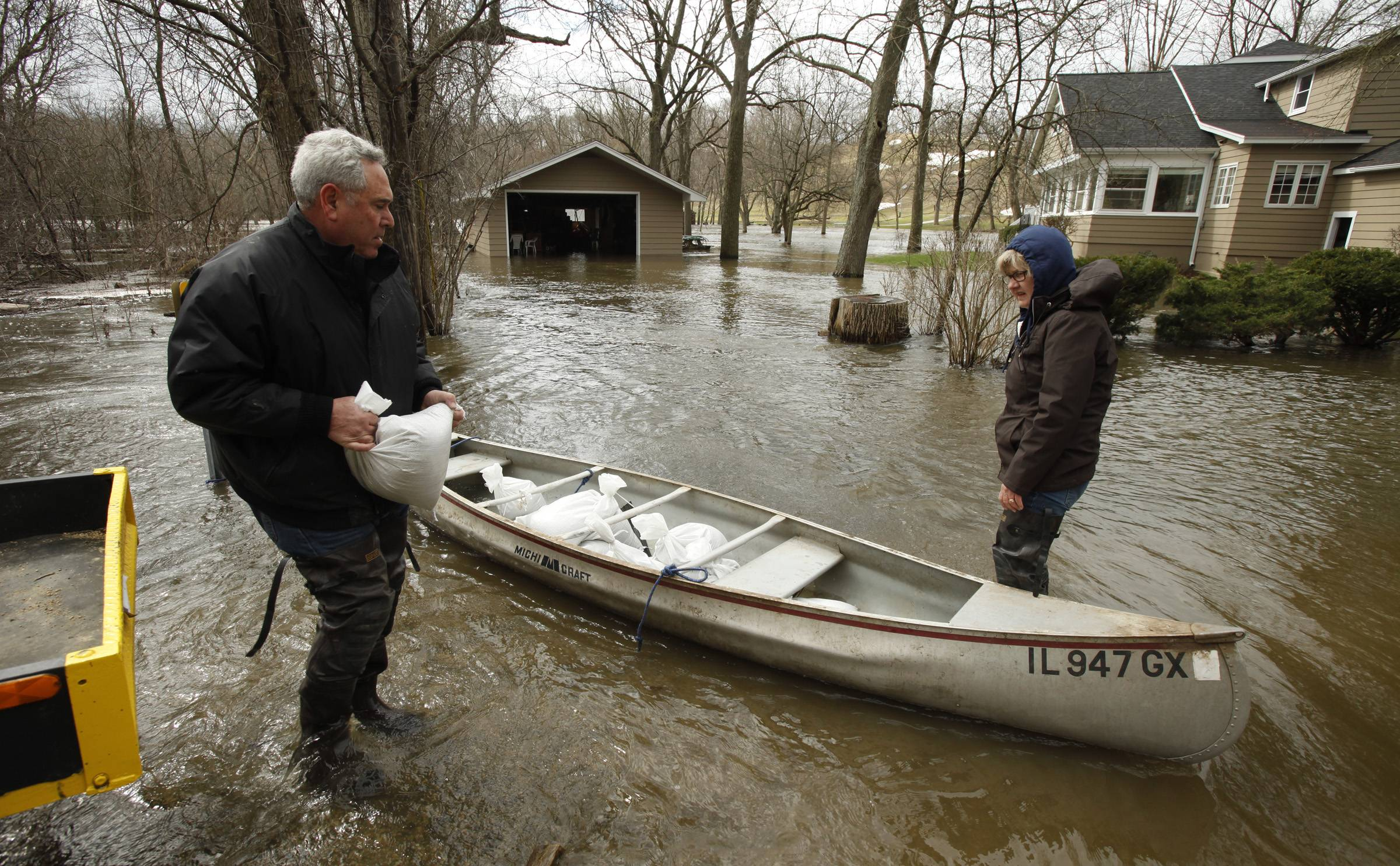 Nick and Nan Gagliano of Algonquin load sand bags into a canoe to make it easier to get the to their home along the Fox River, seen in the background.