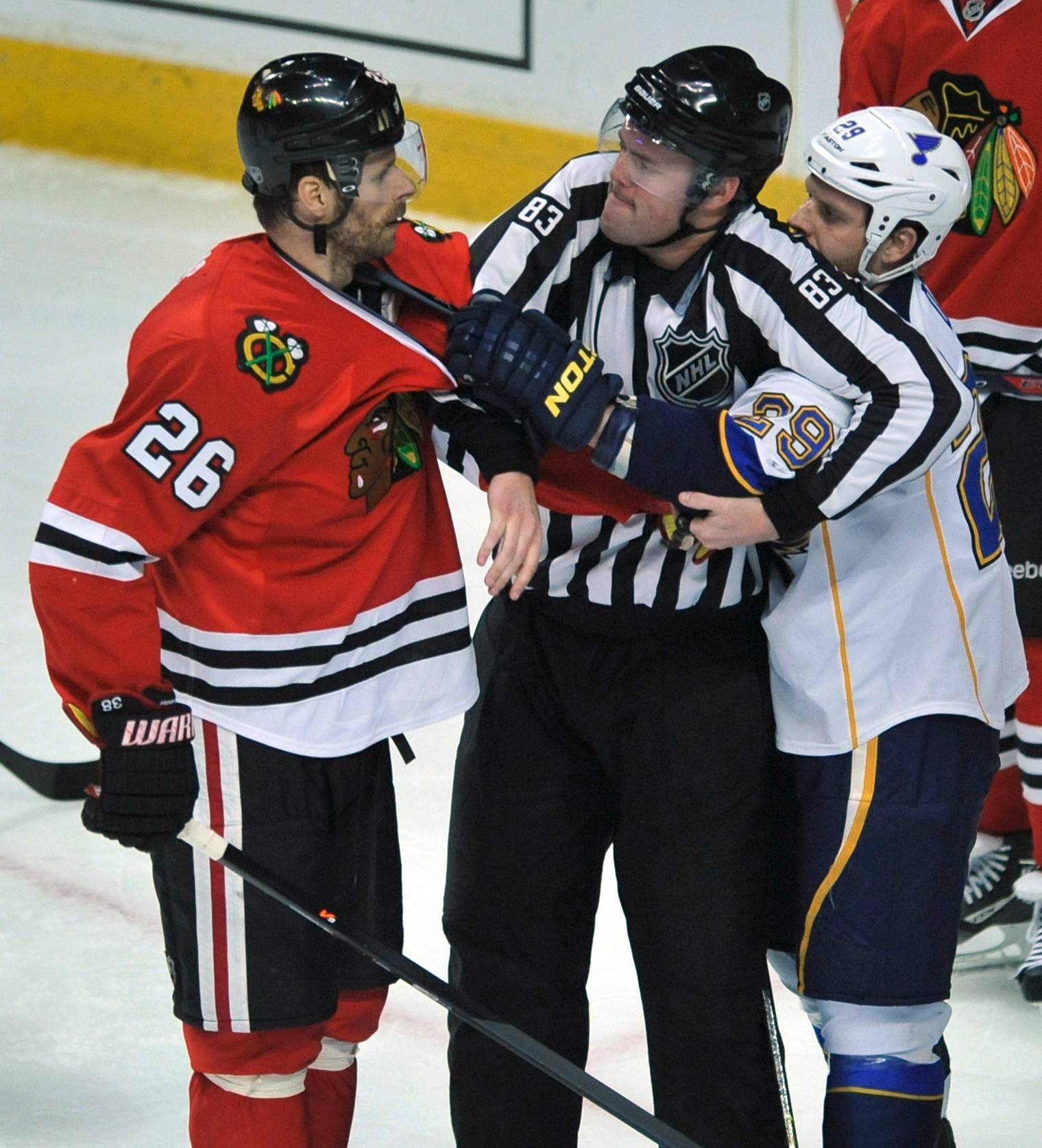 Linesman Matt MacPherson (83), breaks a up a scuffle between Chicago Blackhawks' Michal Handzus (26) and St. Louis Blues' Steve Ott (29) during the second period of an NHL hockey game in Chicago, Wednesday, March, 19, 2014. Chicago won 4-0. (AP Photo/Paul Beaty)