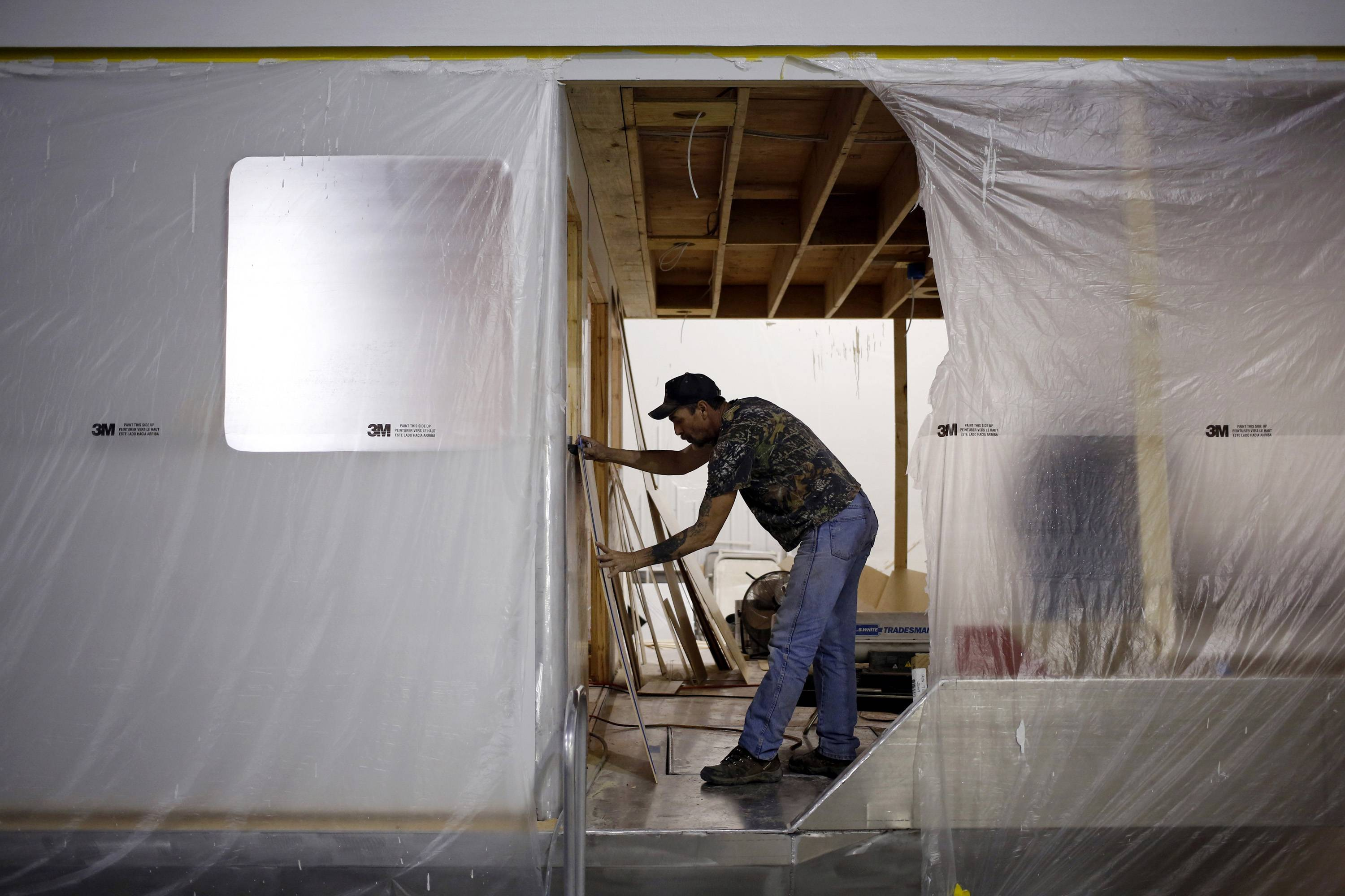 A worker measures wood paneling while working on a custom houseboat at a manufacturing facility in Columbia, Ky. This week's decline in applications for unemployment benefits was a sign employers held the line on firings last week even as cold weather slowed industries from manufacturing to housing.
